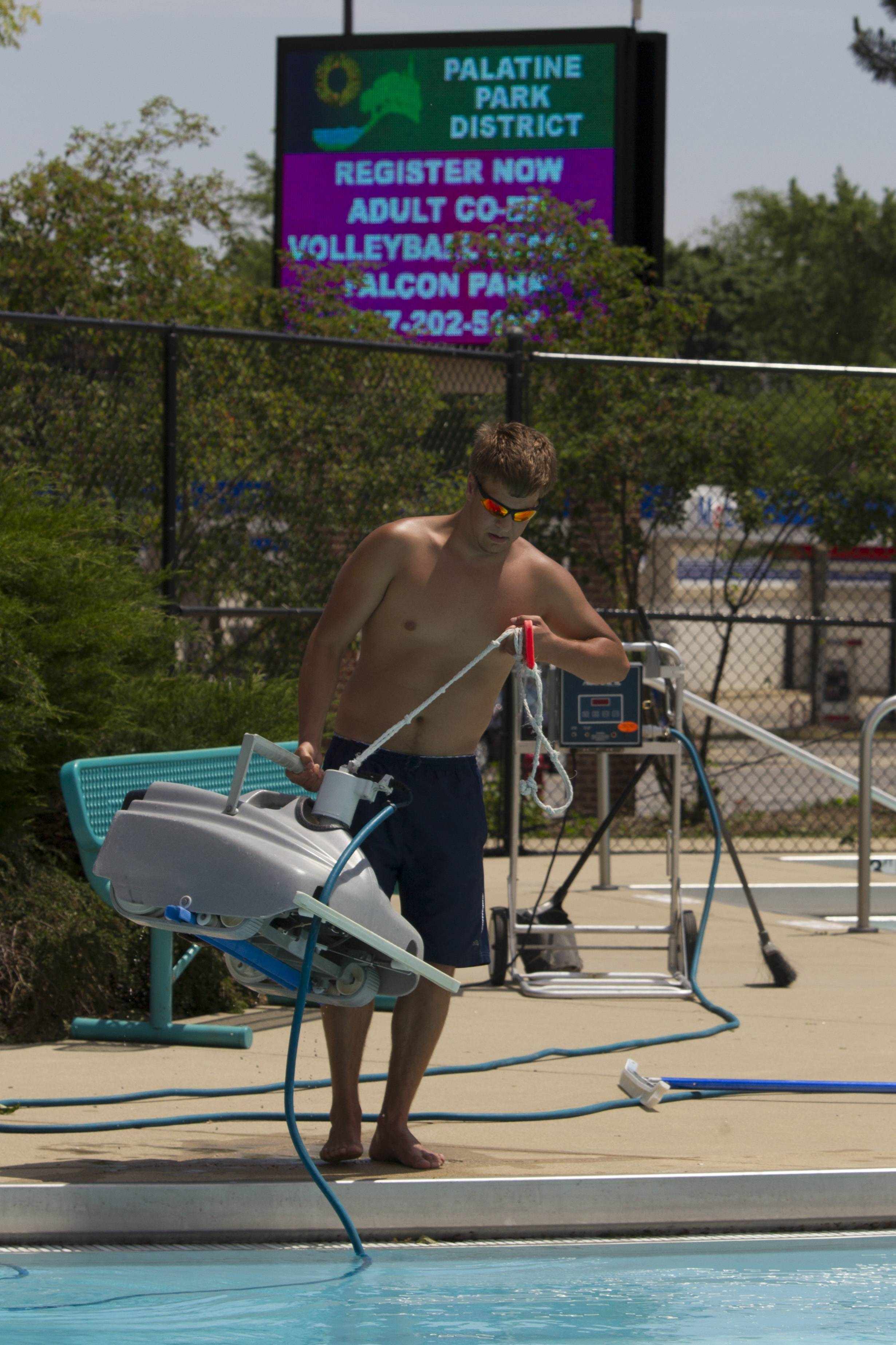 Todd Fauria puts a pool vacuum in the Palatine Family Aquatic Center pool in preparation for its opening at 11 a.m. today.