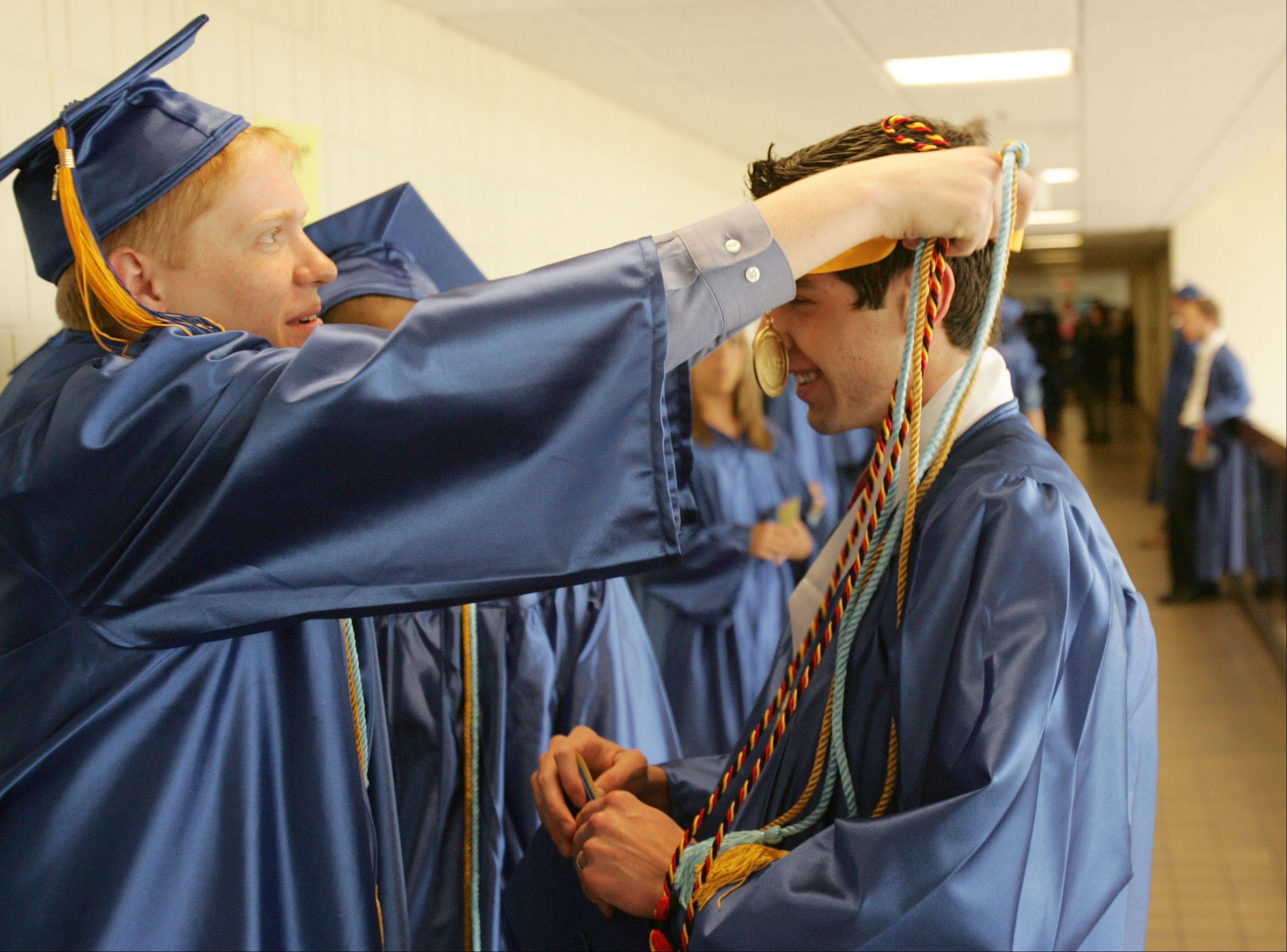 Kevin Salat, left, helps Cody Schulz, right, before the 2012 Wheaton North High School graduation, held at College of DuPage in Glen Ellyn. There were 507 Wheaton North graduates.