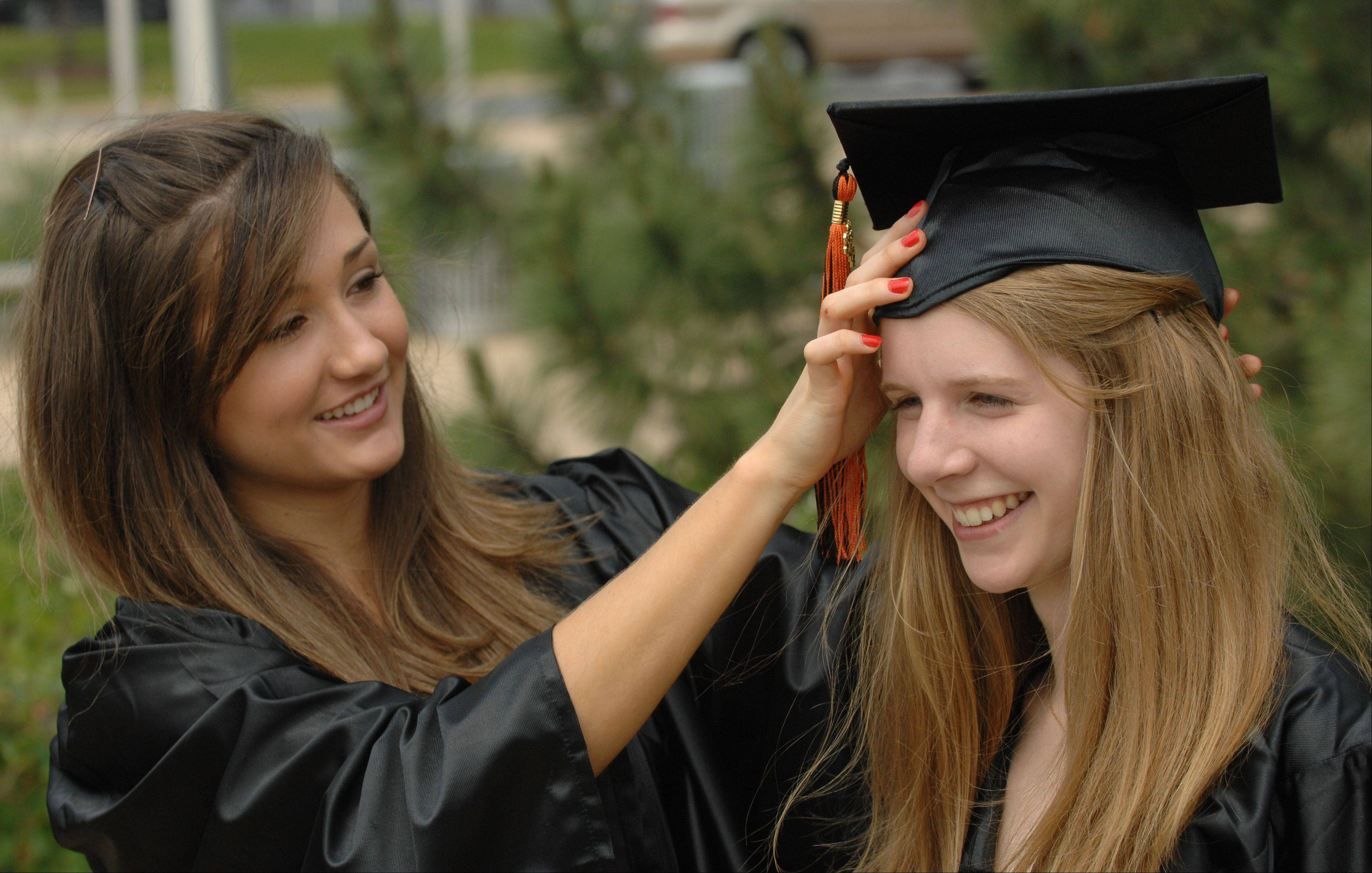 Kinzie Roberton, left, and Laura Hagen get ready Saturday for the Wheaton Warrenville South Graduation at College of DuPage. They are both from Wheaton.