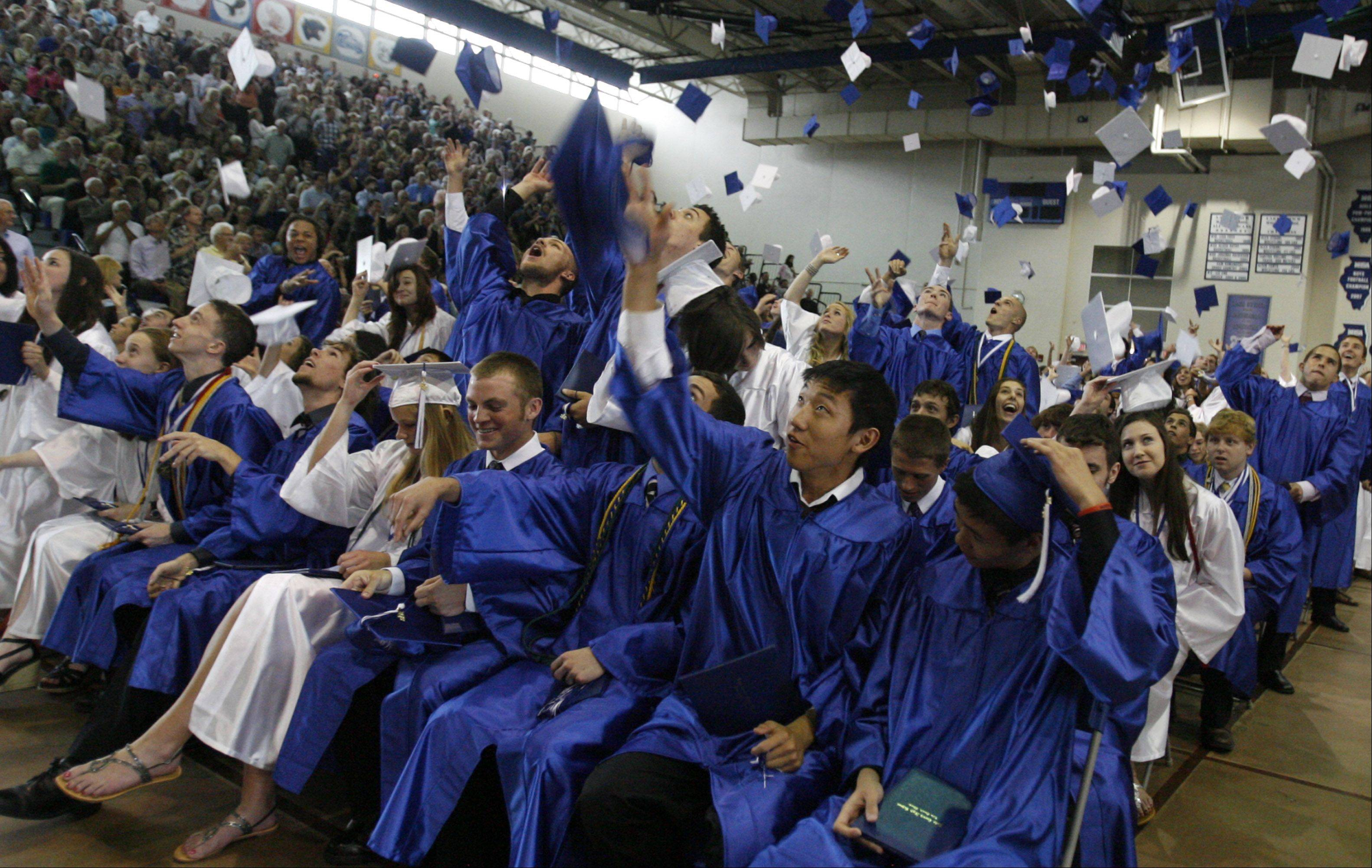 Lake Zurich High School graduates toss their caps at the end of their ceremony on Saturday, May 26.
