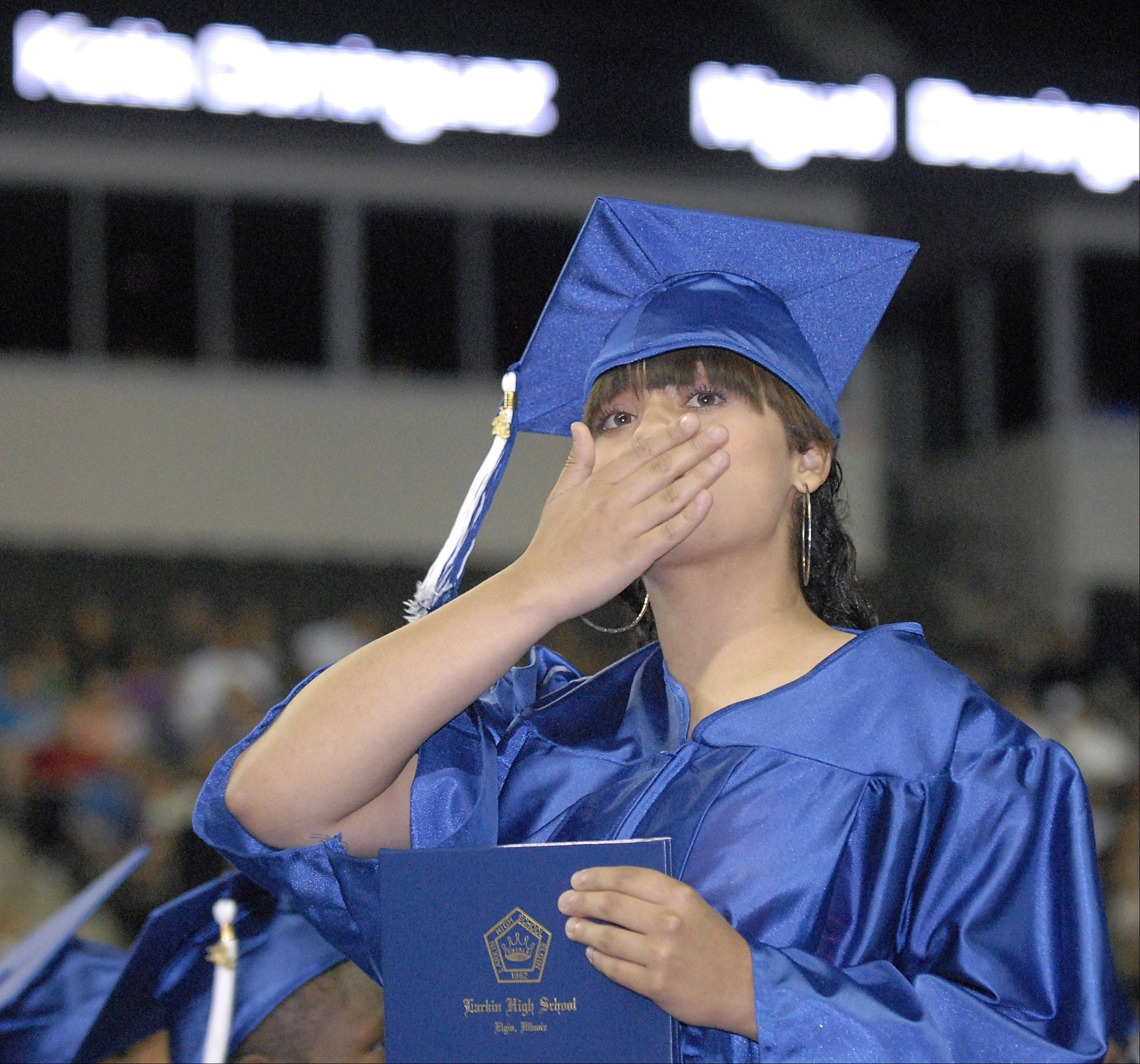 Lisa Rivera blows kisses to her family as she walks back to her seat after receiving her diploma at Larkin High School's commencement ceremony.