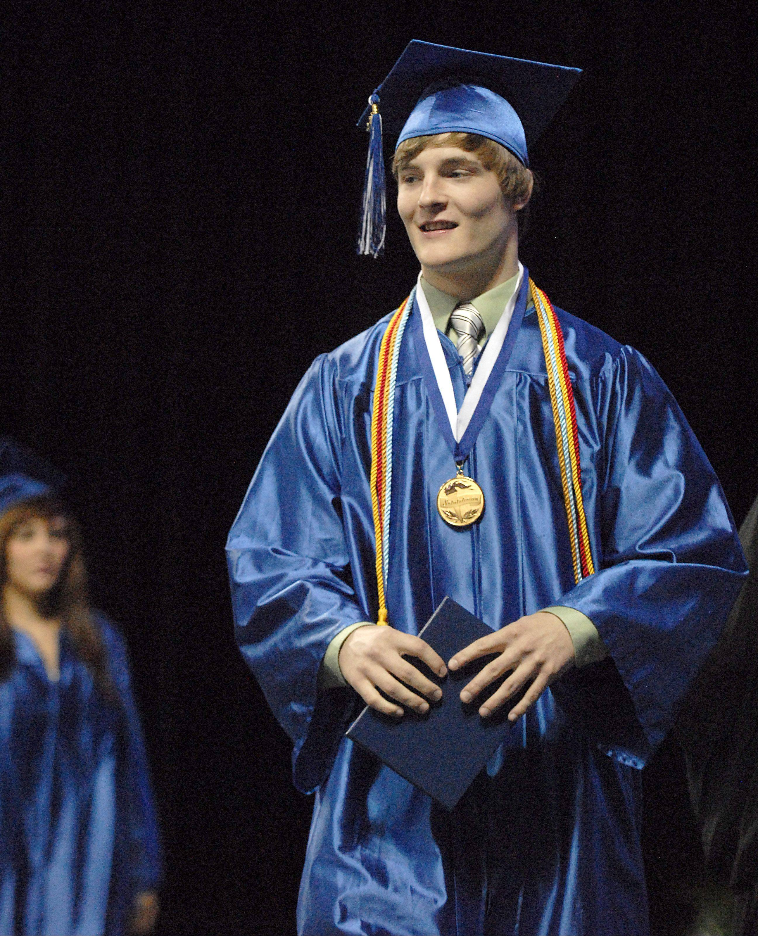 Brett Barry walks off stage with diploma in hand at Larkin High School's commencement ceremony.