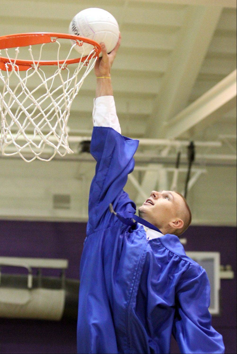Mitch Munda dunks a volleyball in Welsh-Ryan Arena practice gym while preparing for Warren Township High School graduation ceremony at Northwestern University's Welsh-Ryan Arena in Evanston on Saturday, May 26.