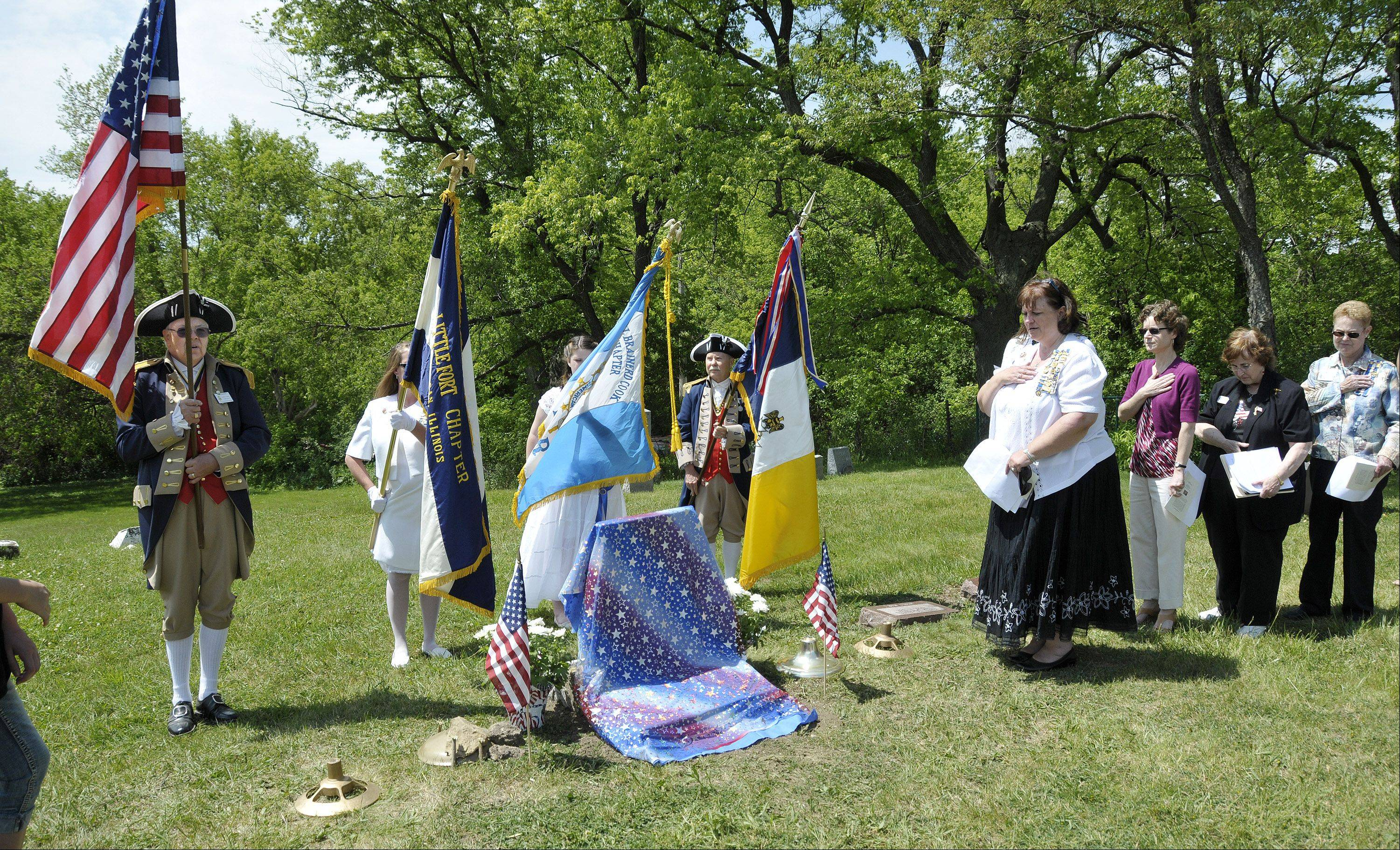 DAR members, at right, say the Pledge of Allegiance, along with the color guard, including members in Revolutionary War uniforms, from the Fox Valley Chapter of the Sons of the American Revolution from Lisle and Naperville.