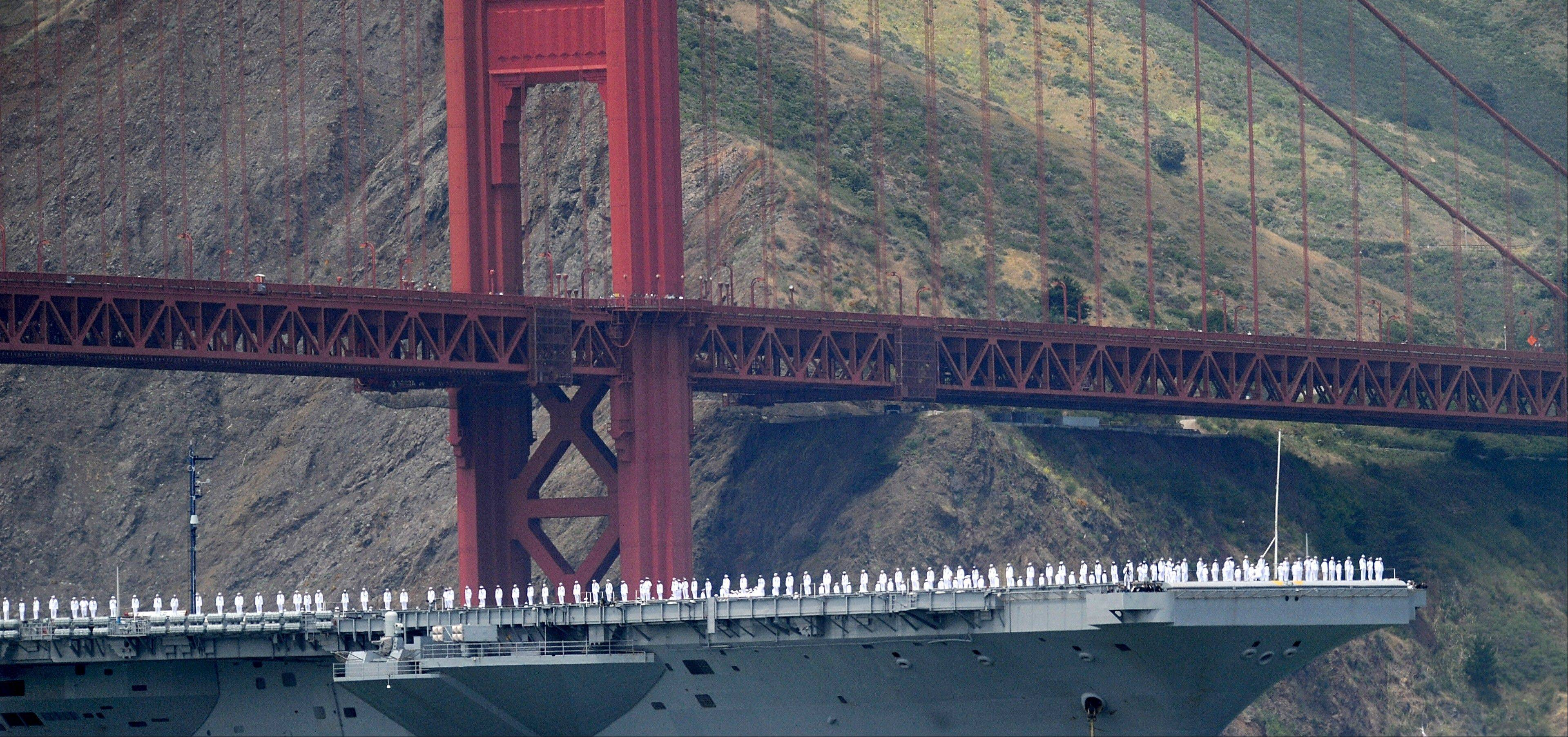 With sailors on deck, the USS Nimitz passes beneath the Golden Gate Bridge during a celebration of the bridge's 75th anniversary Sunday in San Francisco. The commemoration included a vintage car show, an exhibit of roughly 1,558 pairs of shoes representing people who have committed suicide by jumping from the span, and a fireworks display slated for evening.