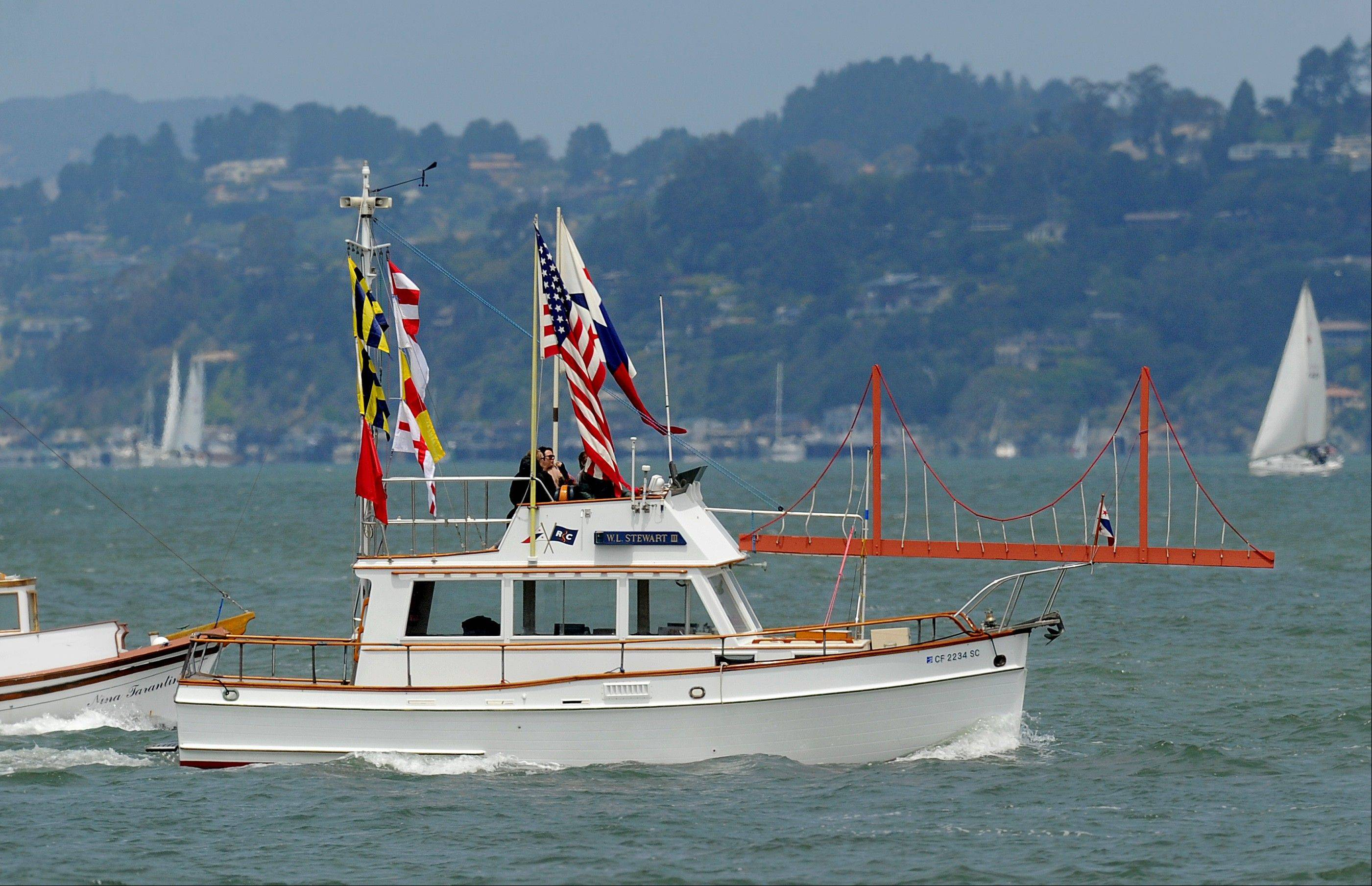 With a sculpture of the Golden Gate Bridge adorning her foredeck, the W.L. Stewart III rides in a boat parade celebrating the Golden Gate Bridge's 75th anniversary on Sunday in San Francisco. The commemoration included a vintage car show, an exhibit of roughly 1,558 pairs of shoes representing people who have committed suicide by jumping from the span, and a fireworks display slated for evening.