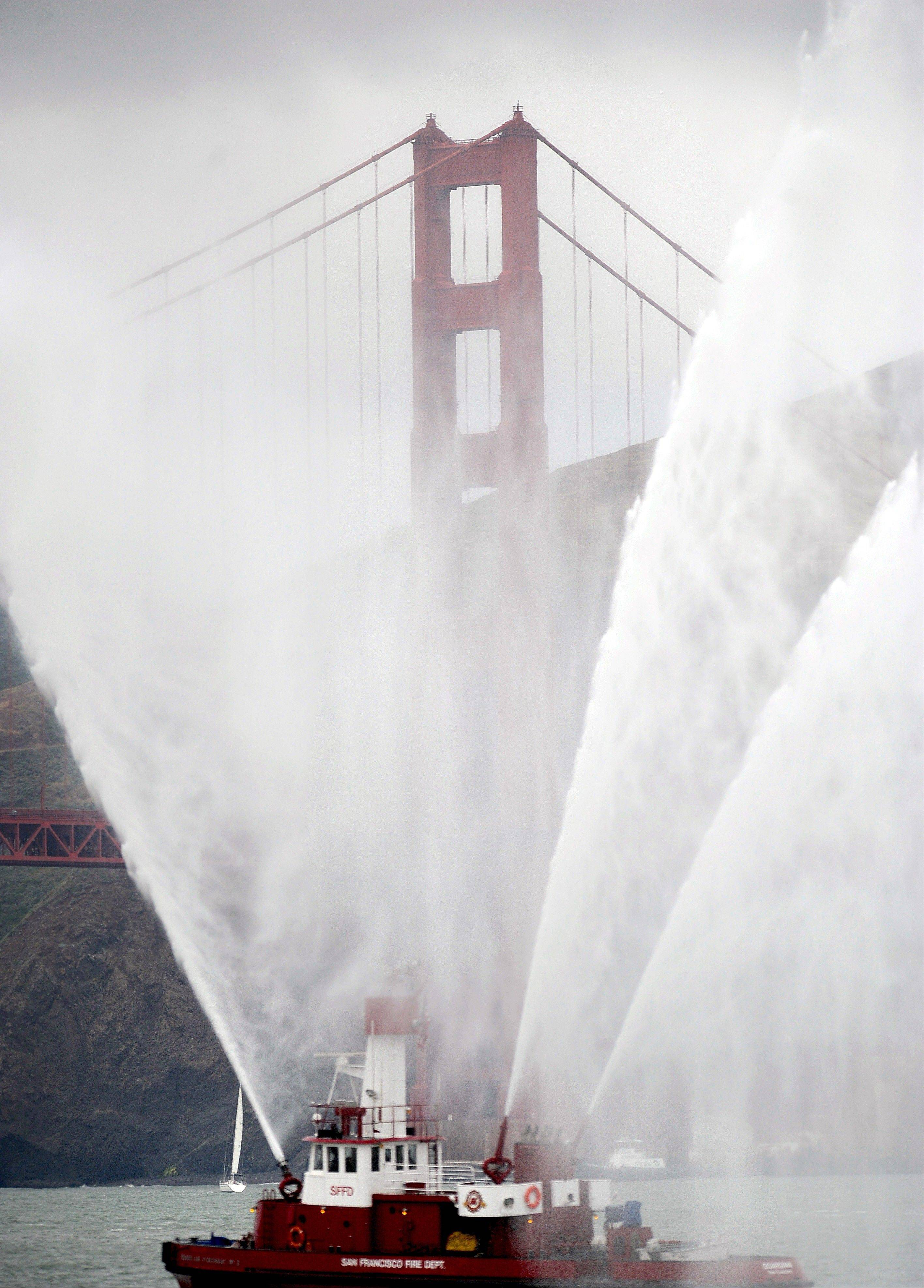 The Phoenix fireboat sprays plumes of water as part of the Golden Gate Bridge's 75th anniversary celebration Sunday in San Francisco. The commemoration included a vintage boat parade and a fireworks display slated for the evening.
