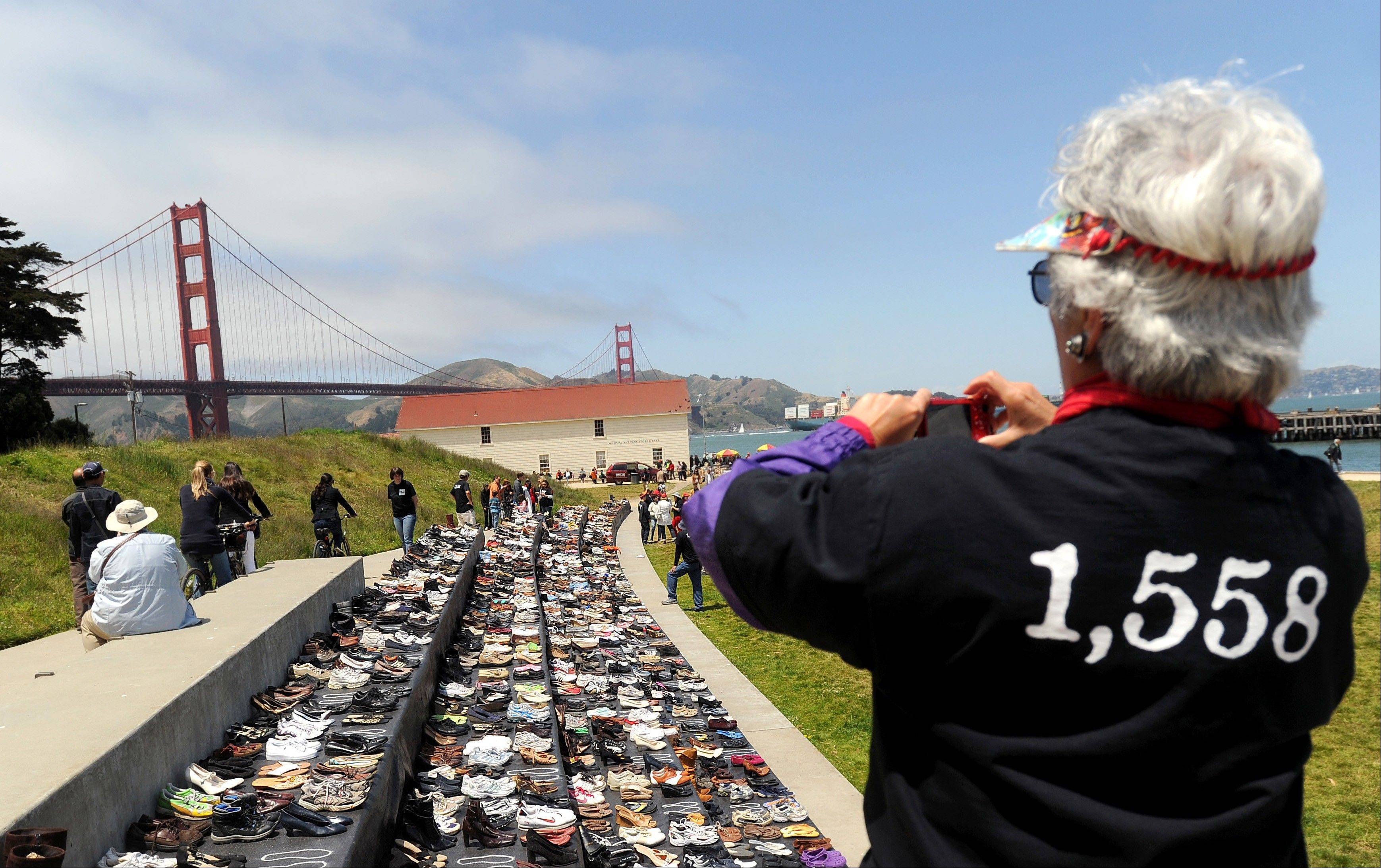 Roberta McLauglin photographs an exhibit of shoes Sunday in remembrance of people who have jumped from the Golden Gate Bridge. The Bridge Rail Foundation, which advocates for a safety net along the span to prevent suicides, estimates about 1,558 people have died after jumping since the bridge opened.
