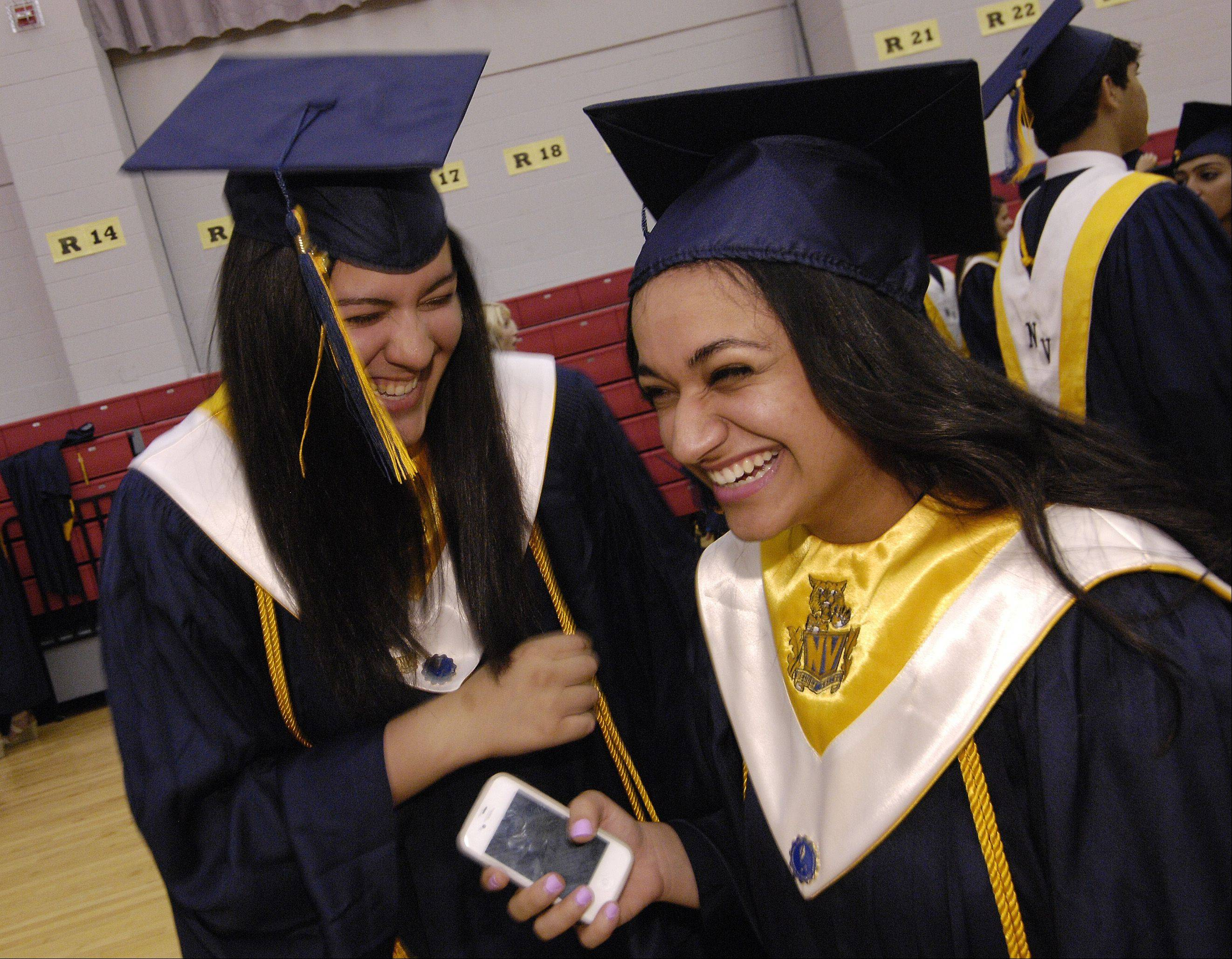 Armita Manafzadeh and Nava Lalehzari share a laugh before the start of the 2012 Neuqua Valley High School graduation Sunday in DeKalb at the NIU Convocation Center.