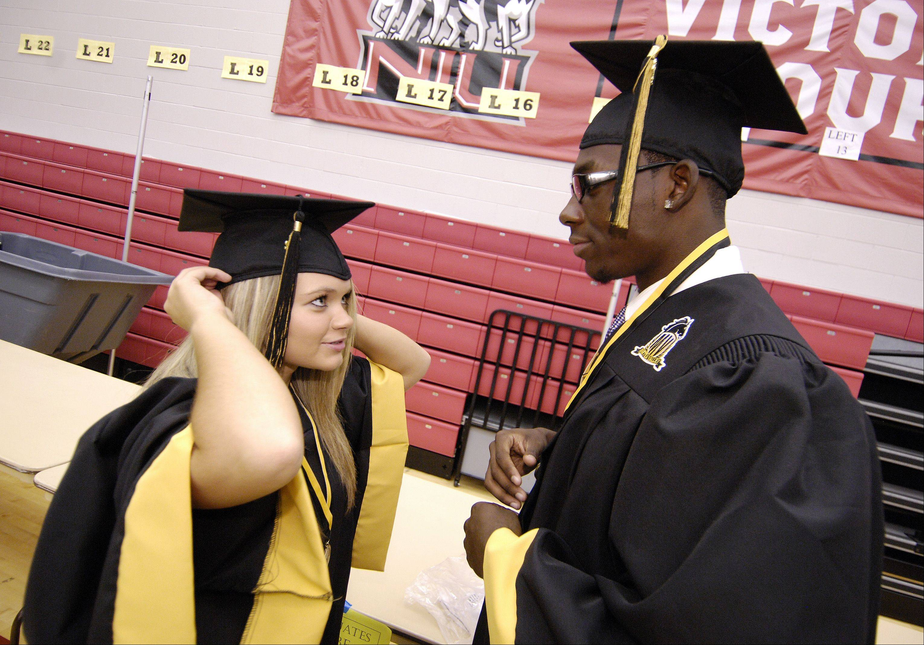 Morgan Parise and Ray Parker get ready for Metea Valley High School's inaugural graduation Sunday in DeKalb at the NIU Convocation Center.