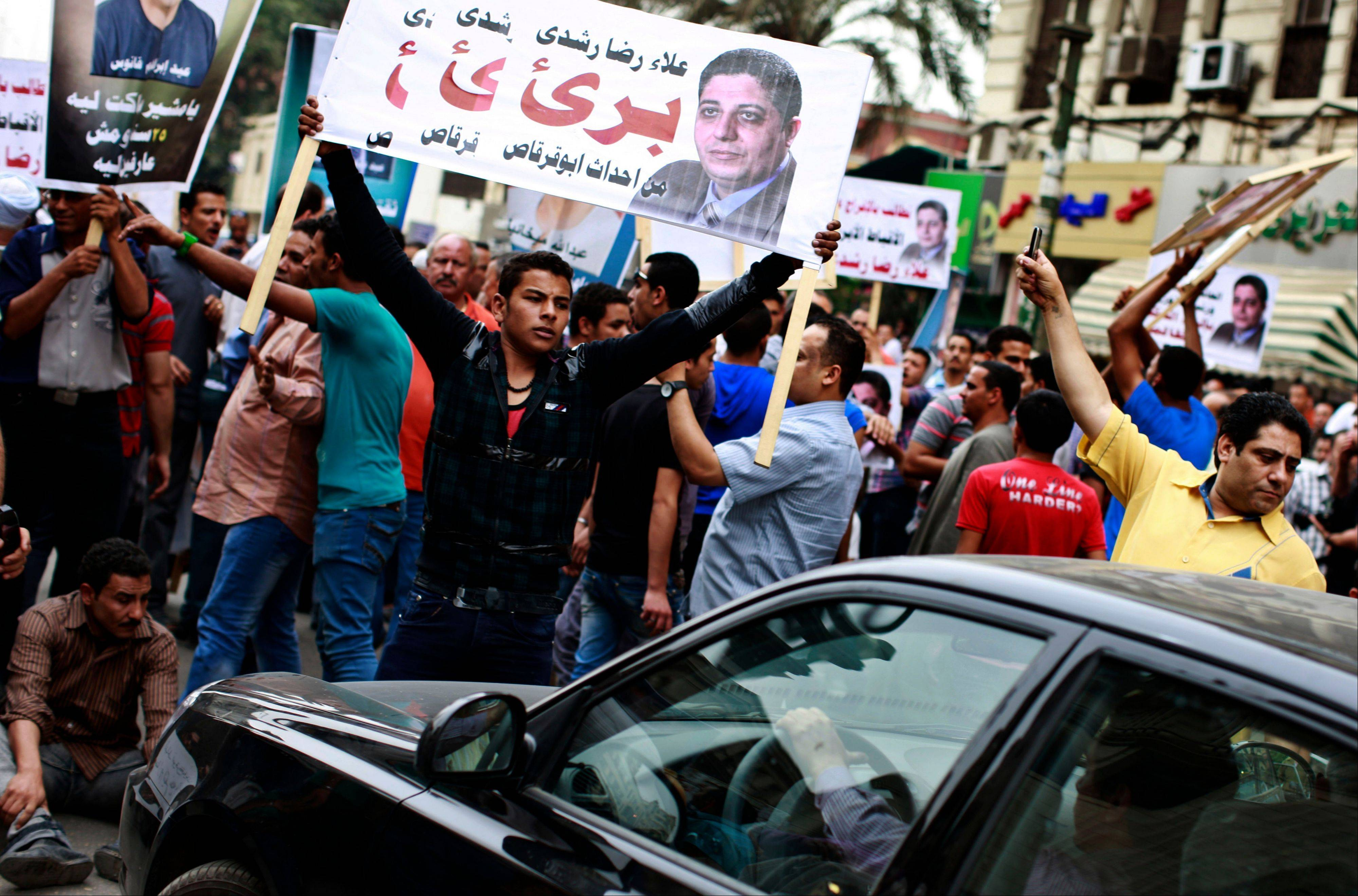 "Egyptian Coptic Christians chant slogans and hold a banner with Arabic that reads, ""Alaa Reda Roshdy is innocent,"" at a protest calling for the release of Copts held in jails for political reasons in downtown Cairo, Egypt, on Sunday."