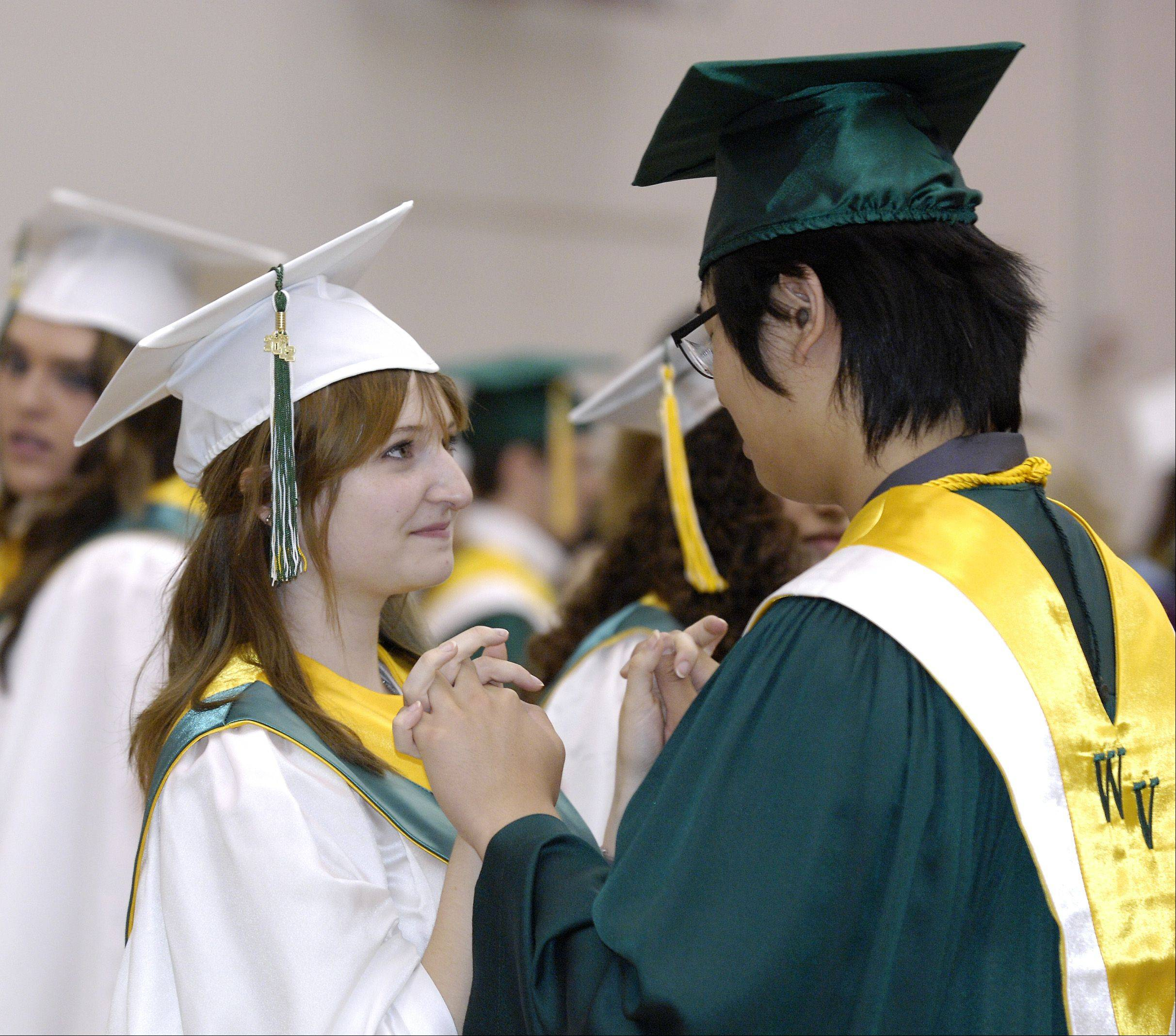 Mariah Brito and Seong Ju Kim have a moment before the start of Waubonsie Valley High School's graduation Sunday in DeKalb at the NIU Convocation Center.
