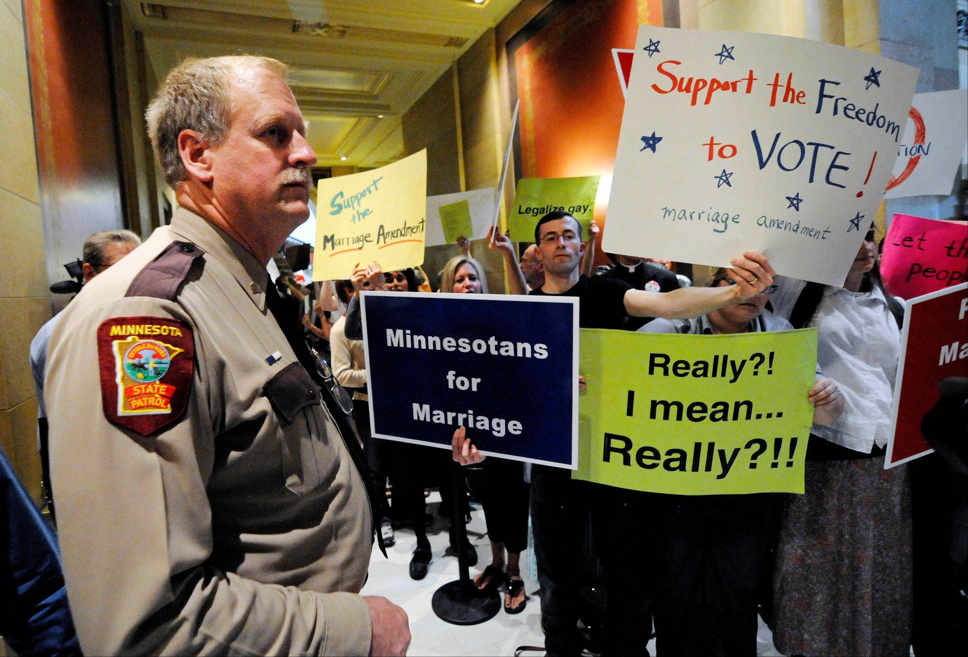 A state trooper stands by as demonstrators on both sides of the gay marriage issue gather outside the Minnesota House in St. Paul, Minn. Poll after poll shows public support for same-sex marriage steadily increasing, to the point where it's now a majority viewpoint. Yet in all 32 states where gay marriage has been on the ballot, voters have rejected it. It's possible the streak could end in November 2012, when Maine, Maryland, Minnesota and Washington state are likely to have closely contested gay marriage measures on their ballots. For now, however, there remains a gap between the national polling results and the way states have voted.