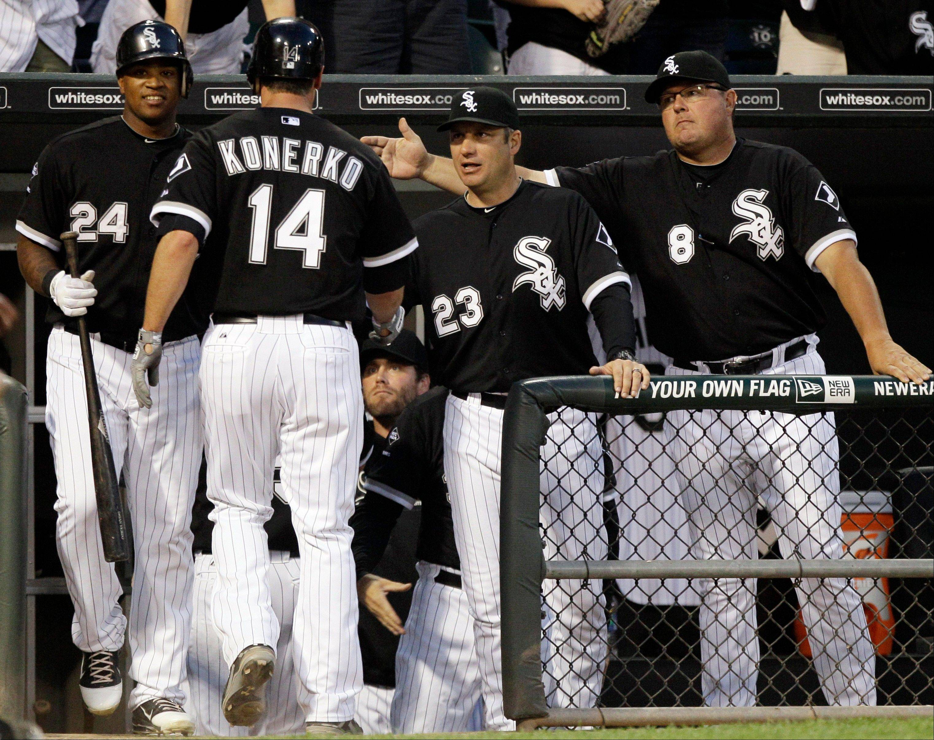 White Sox slugger Paul Konerko (14) is congratulated by manager Robin Ventura (23), bench coach Mark Parent (8) and Dayan Viciedo (24) after scoring on a double by Alex Rios (51) during the third inning of a baseball game against the Minnesota Twins in Chicago, Thursday, May 24, 2012.