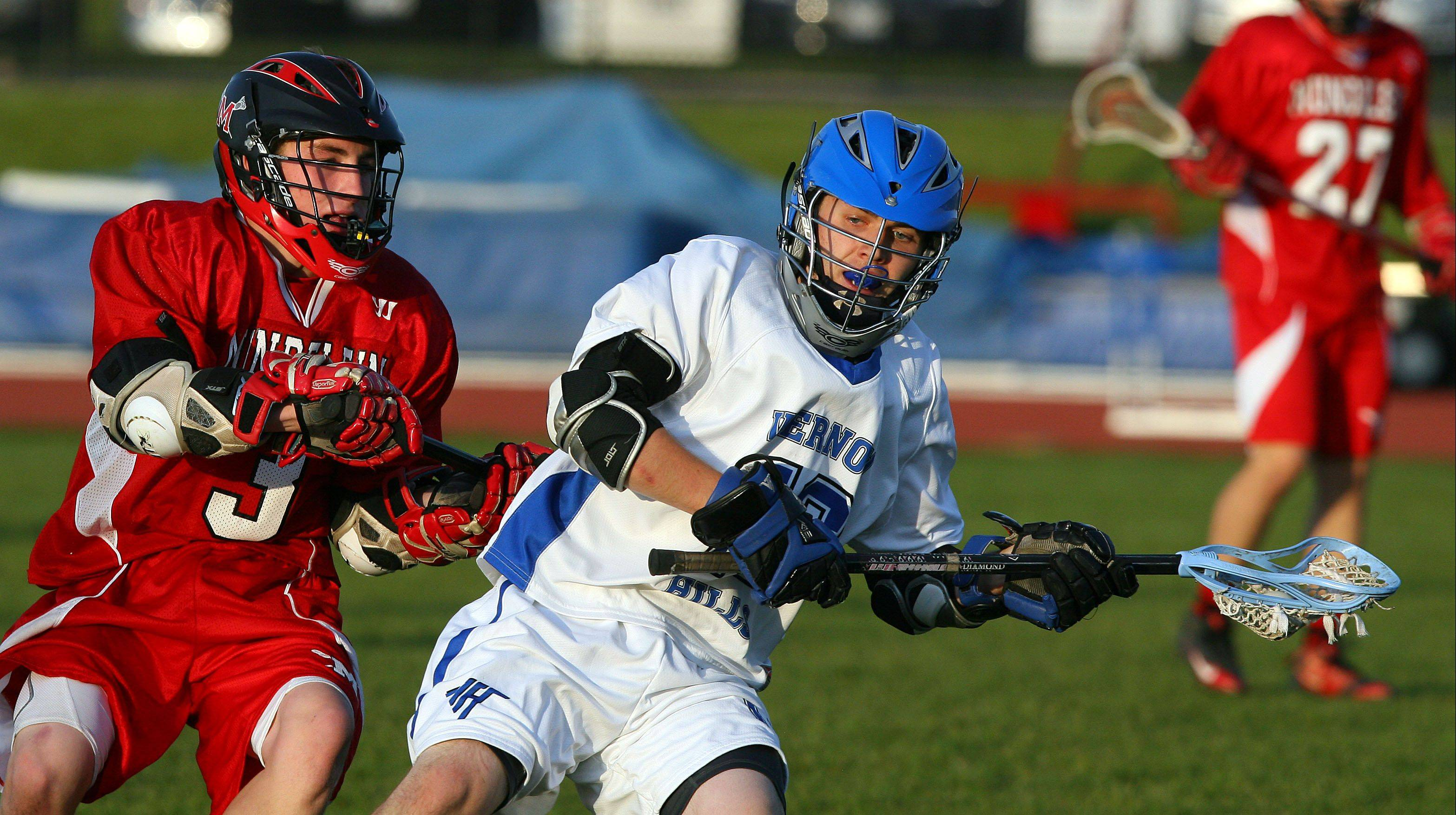 Mundelein's Hunter Ebdon, left, and Vernon Hills' Phillips Brown battle for the ball.