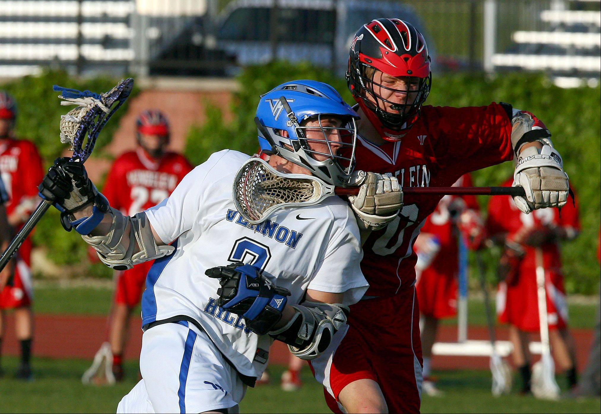 Vernon Hills' Tyler Peterson, left, drives on Mundelein's Luke Samson.