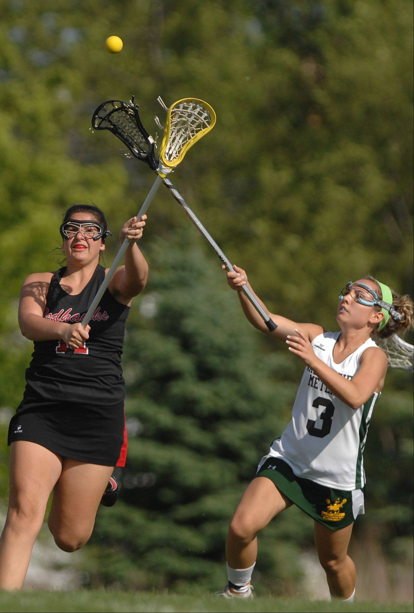 Meaghan Bedigian of Naperville Central, left, and Kim Rowell of Waubonsie/Metea chase down a ball.