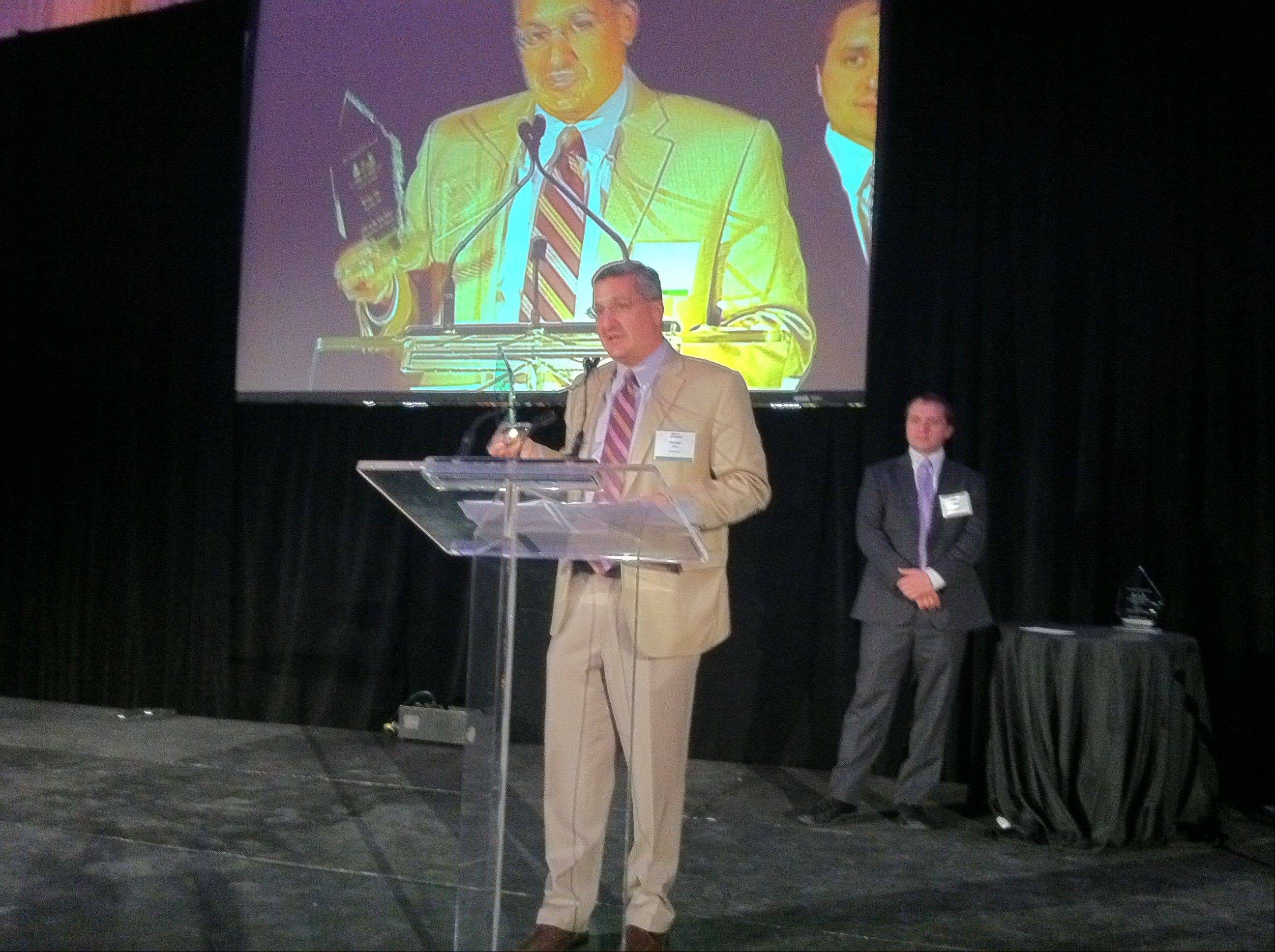 Michael Alter, CEO of SurePayroll, accepts the CEO of the Year Award from the Illinois Technology Association.