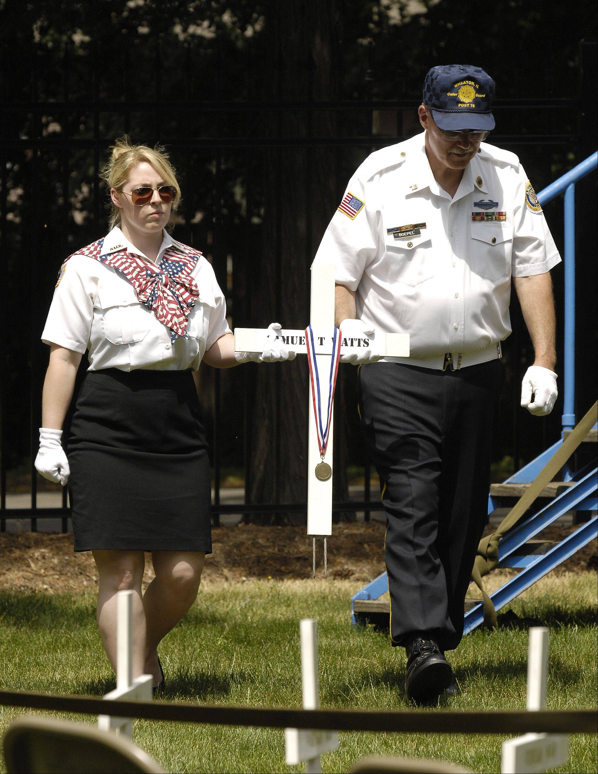Nicolette Laurich, Jr., vice president of the Ladies Auxiliary of Veterans of Foreign Wars Post 2164, and Jim Goepel, of American Legion Post 67 and VFW Post 2164, carry a wooden cross in honor of U.S. Army Spc. Samuel Watts, who died last week from injuries he suffered in April from a roadside bomb in Afghanistan. The city of Wheaton held its annual Memorial Day ceremony at Wheaton Cemetery Monday.
