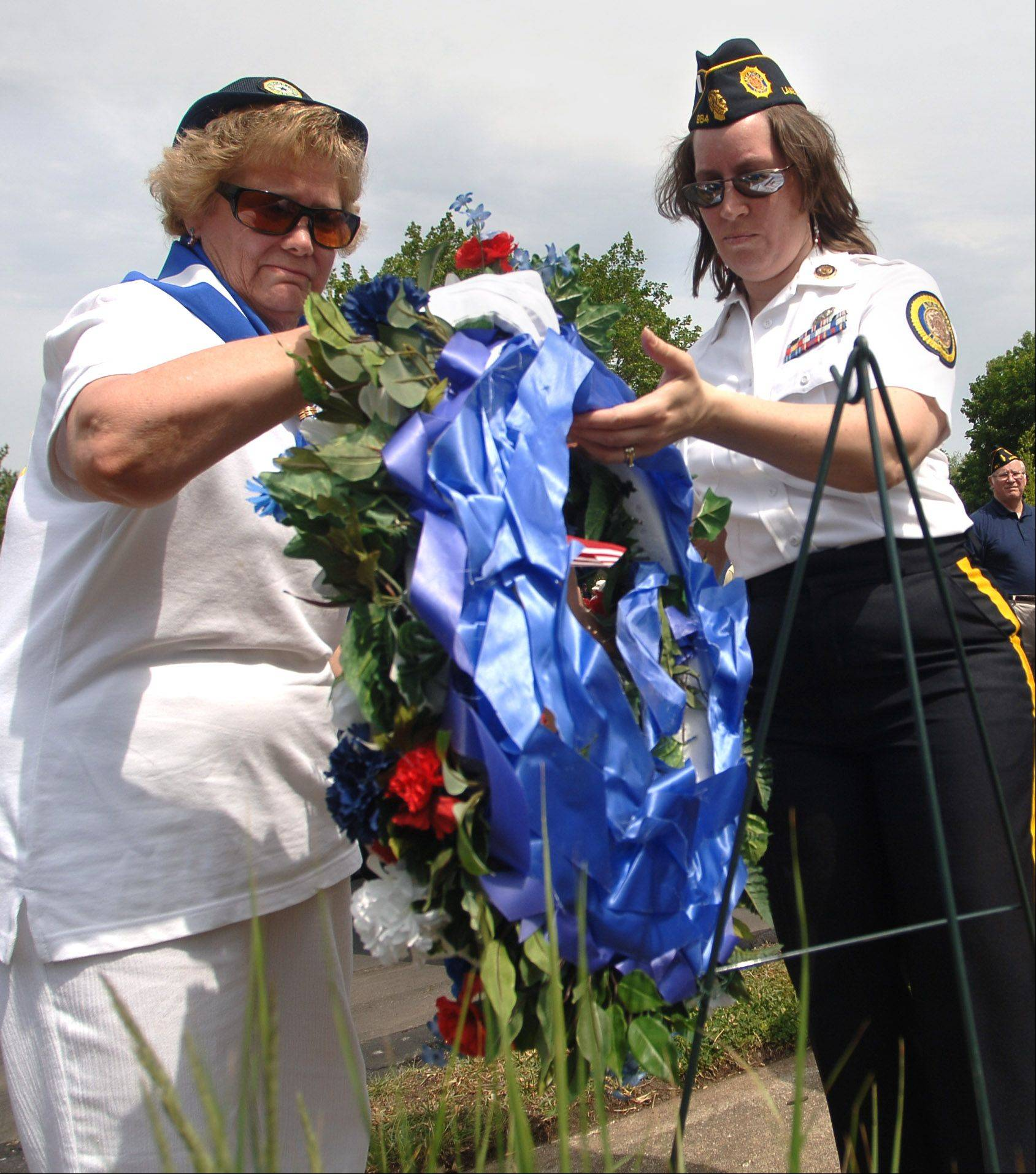Nancy Konz, left, with the Mundelein American Legion Post 867 Auxiliary, and Victoria McConville, with the Lake Zurich American Legion Post 964, present the wreath during Monday's Memorial Day ceremony.