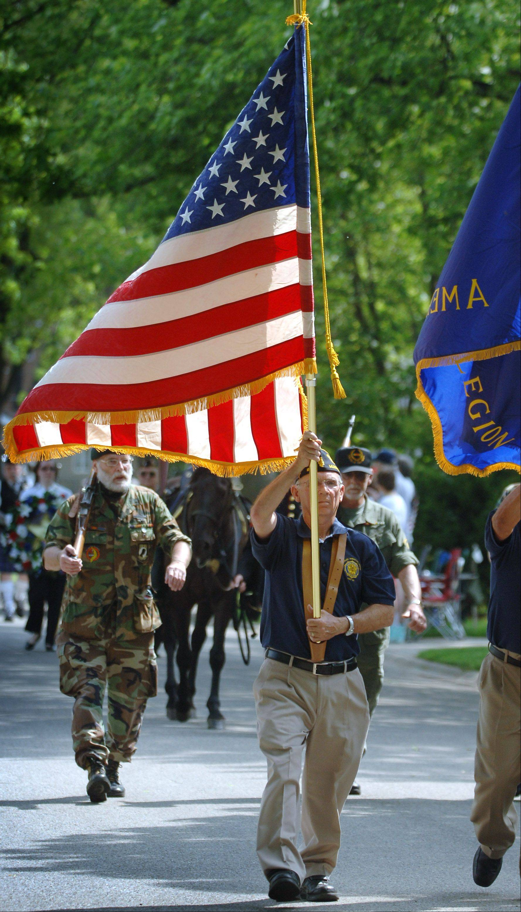 Mundelein's annual Memorial Day parade heads down Pershing Ave. with American Legion Post 867 member Paul Papineau carrying the American Flag.