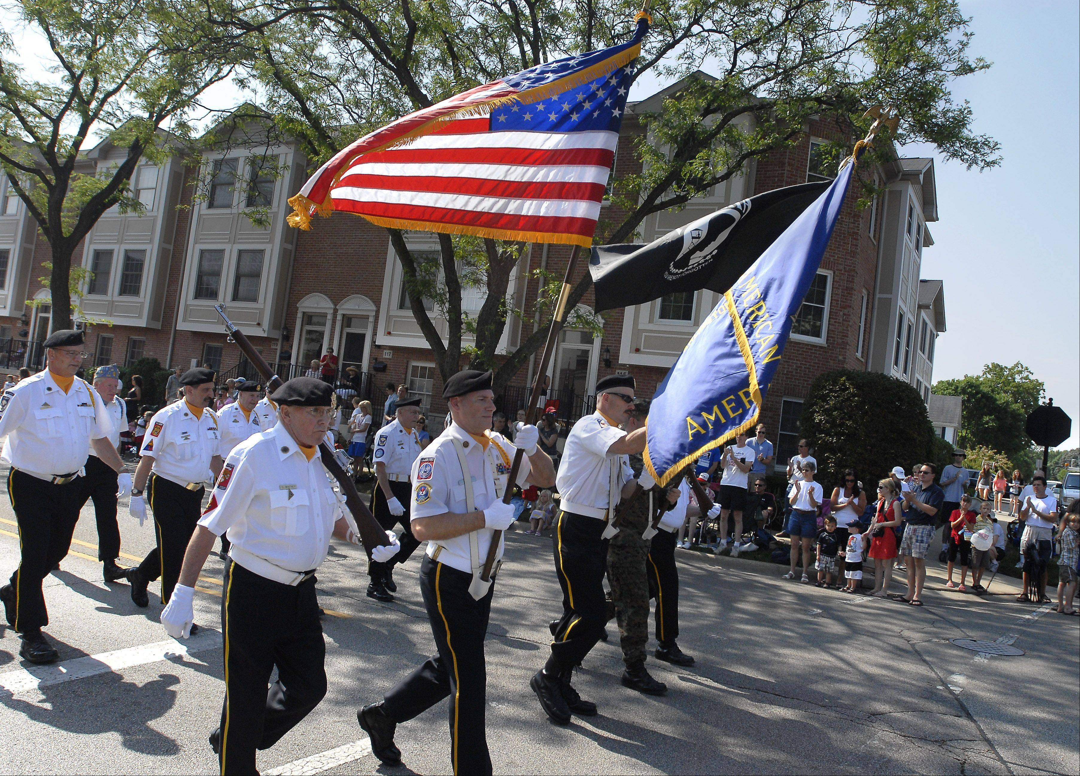 Parade goers stand as members of the Arlington Heights American Legion Merle Guild Post 208 bear the flag at the Memorial Day parade in Monday in Arlington Heights.
