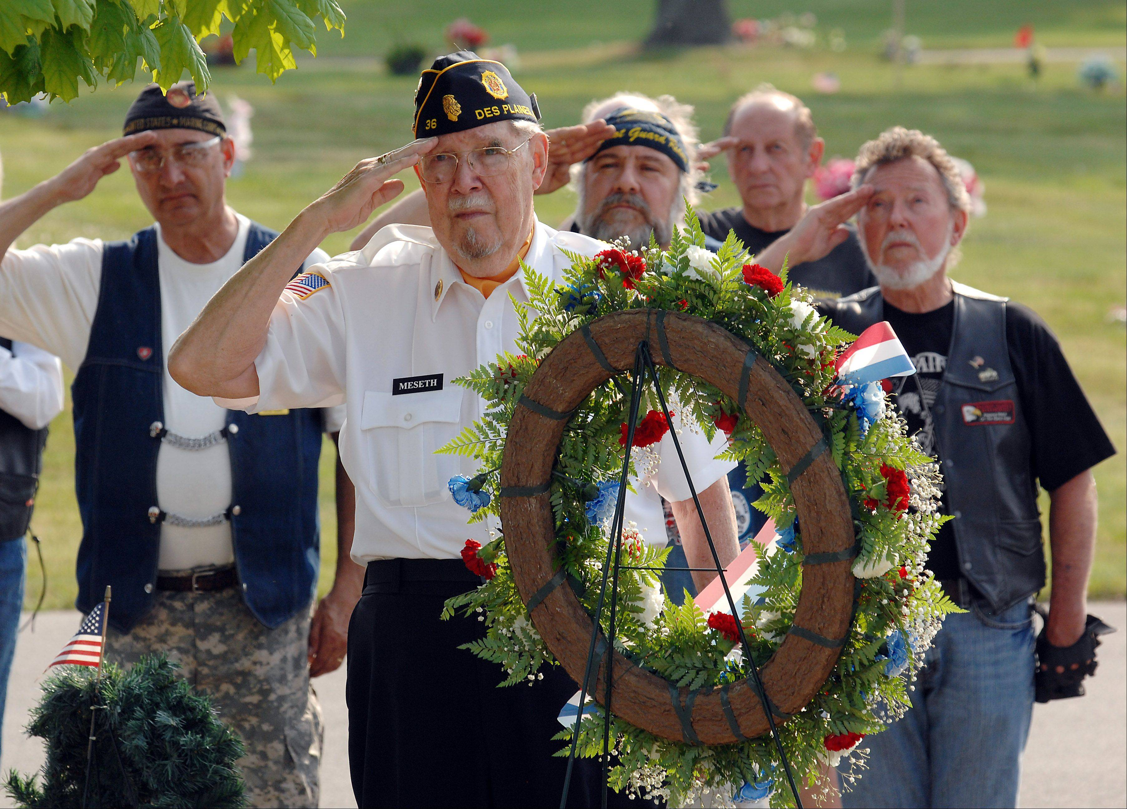 American Legion Post 36 Officer Don Meseth prepares to lay a wreath at the Memorial Day ceremony at All Saints Cemetery in Des Plaines on Monday.