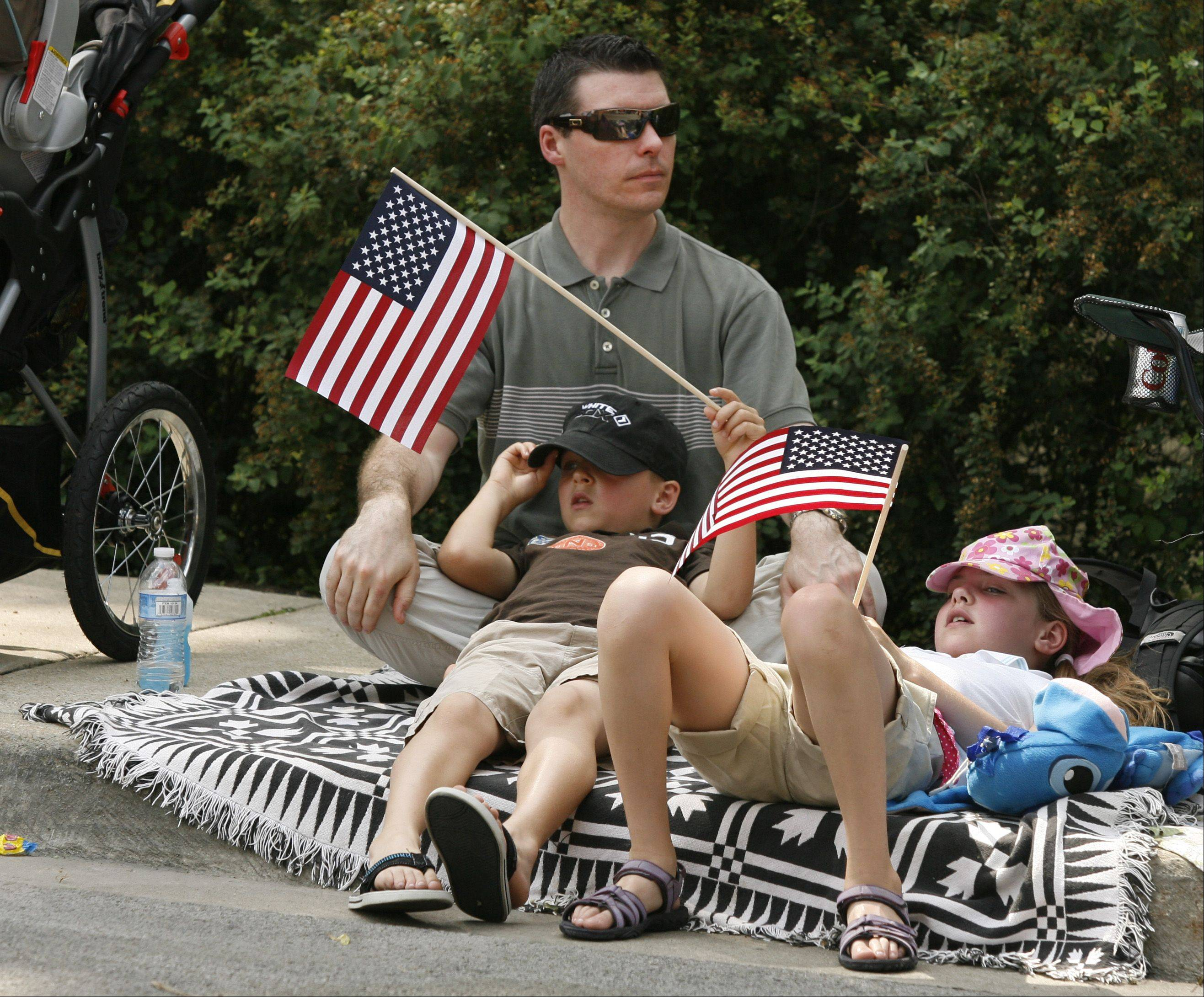 Jason Witte of Naperville relaxes in the shade with his son James, 6, and Charlotte, 8, before the Naperville Memorial Day parade.