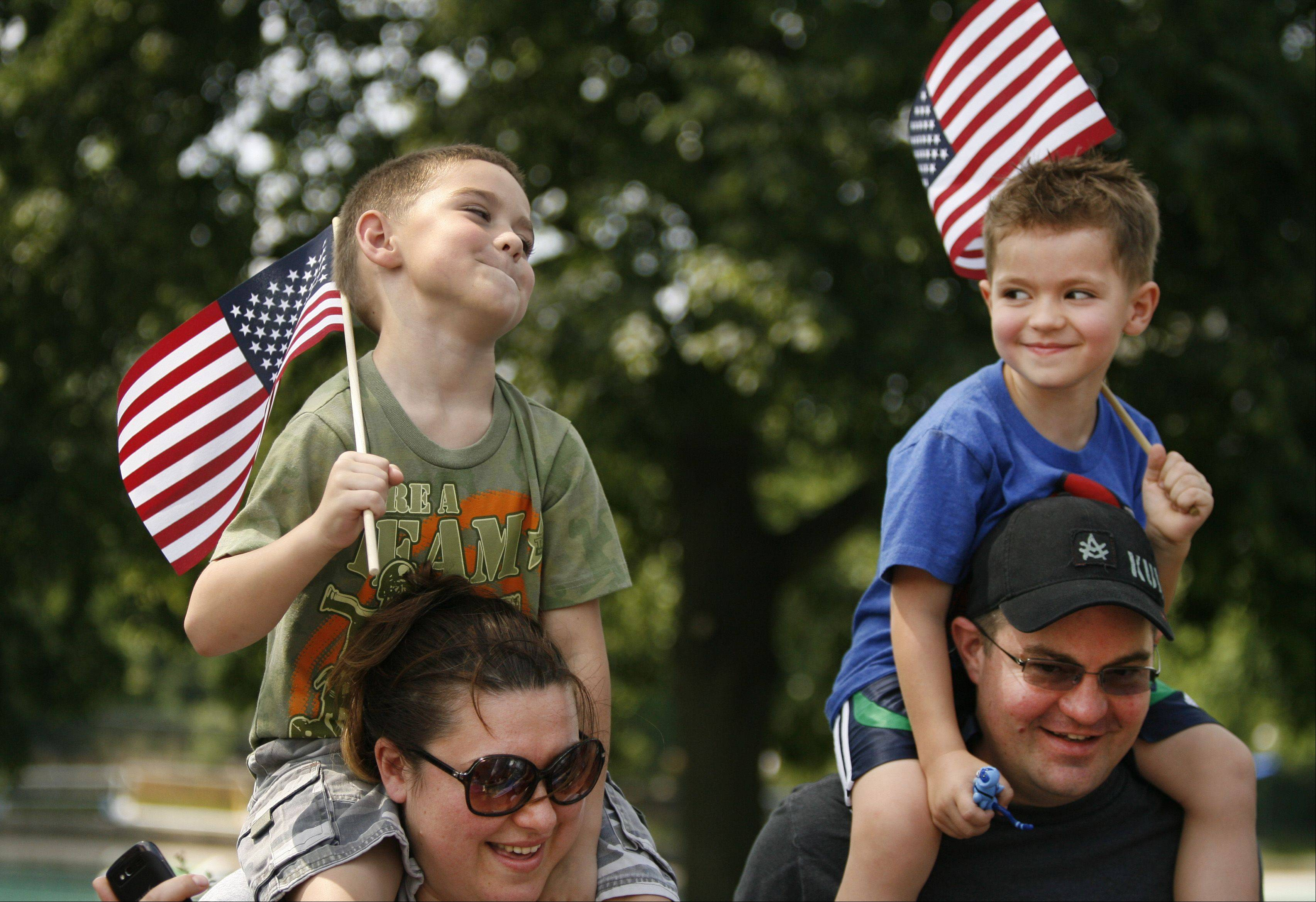 Jasmina and John O'Connor of Naperville give their boys Milan, 5, and Nikola, 4, a higher view to watch the Naperville Memorial Day parade.