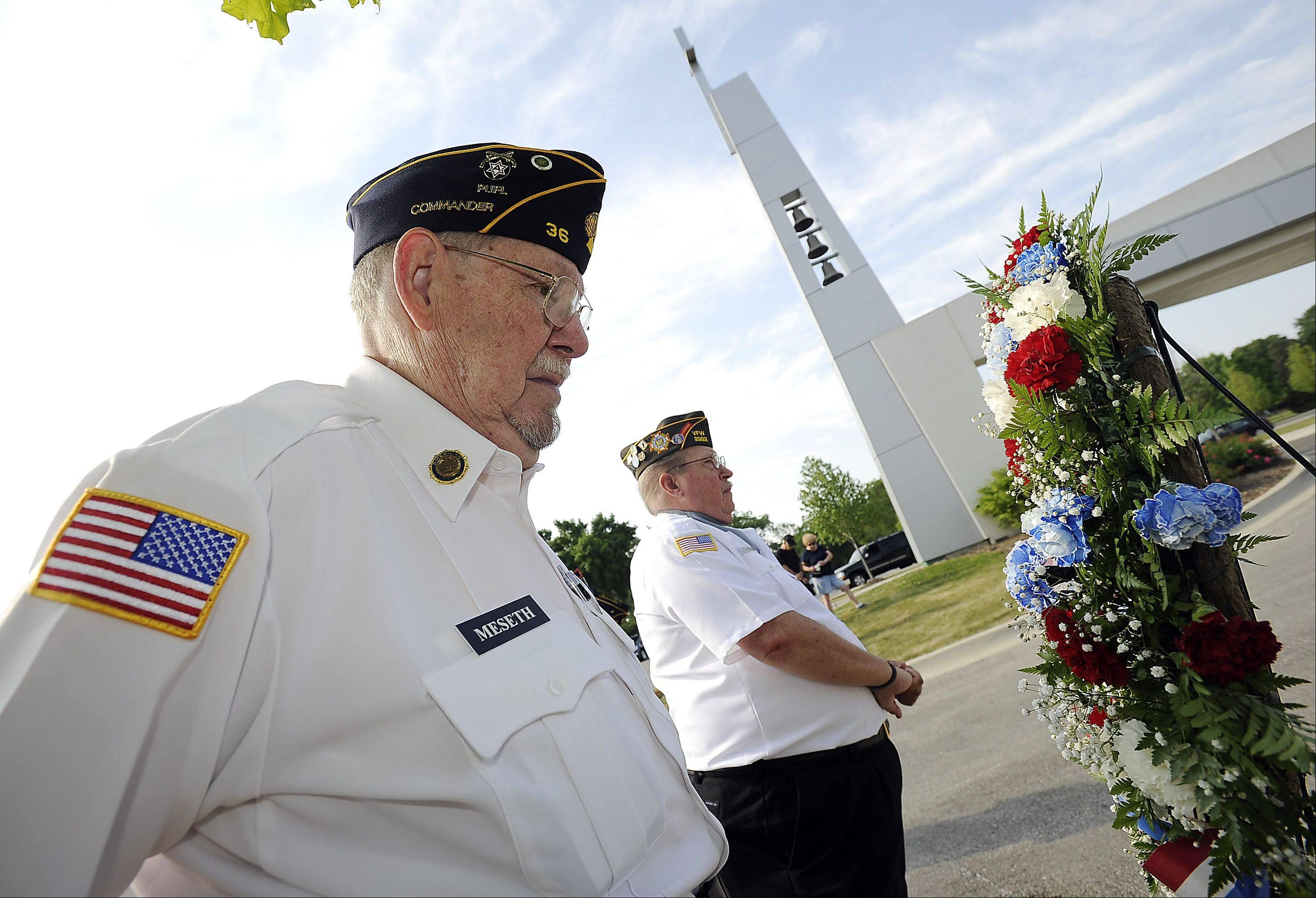 VFW 2992 Commander Willain Fiegel, right, along with Officer Don Meseth of American Legion Post 36 prepare to lay a wreath at the Memorial Day ceremony at All Saints Cemetery in Des Plaines on Monday.