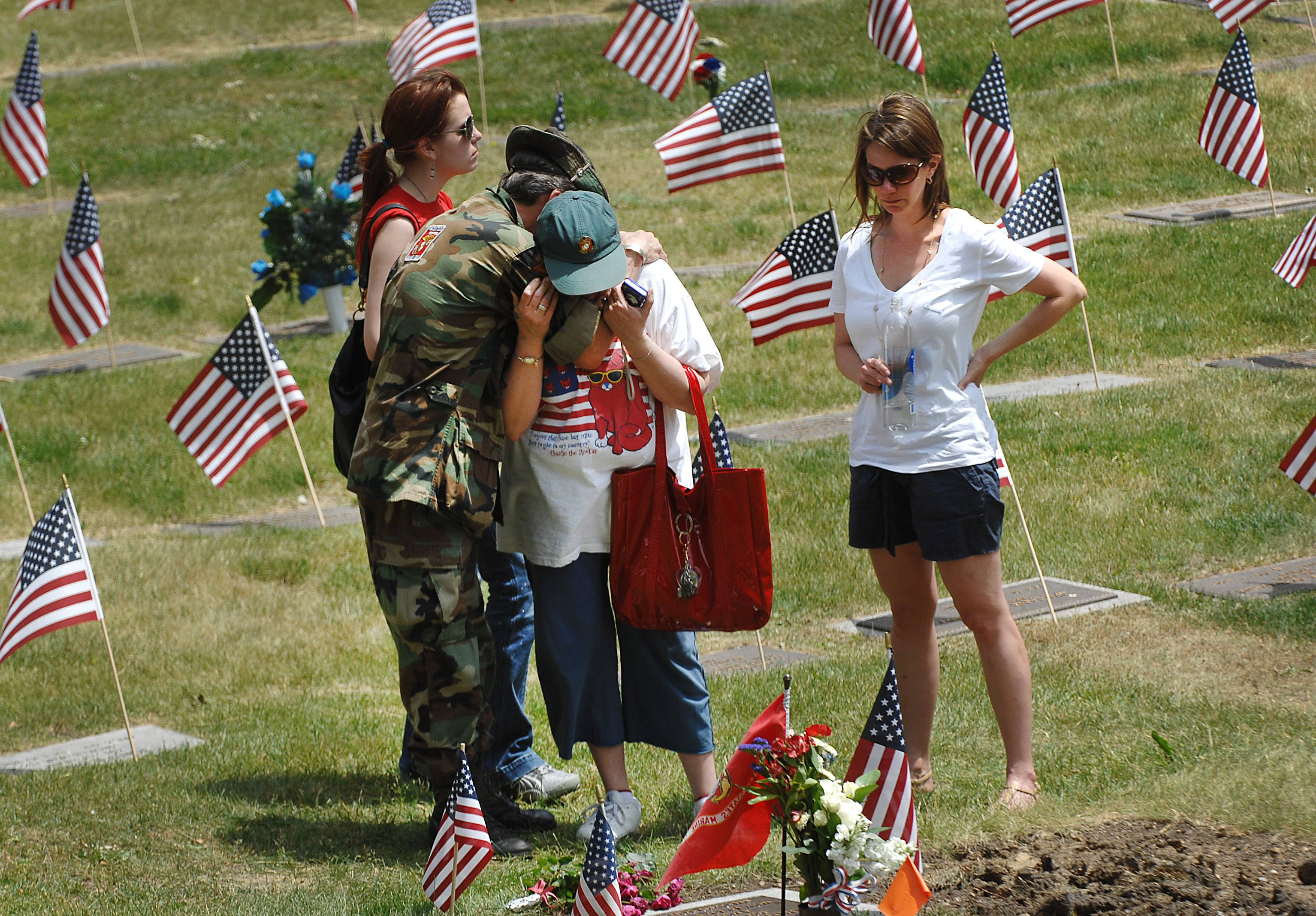 James Corcoran hugs his wife Gayle as they stand at their son John's grave Monday at the Bluff City Cemetery following the Memorial Day service in Elgin. The 33-year-old Corcoran served in the Marine Corps for eight years in Iraq, Afghanistan, Somalia and several other conflicts. He suffered from Post Traumatic Stress Disorder and killed himself last year after returning to Elgin. His sisters Caroline and LIsa, right, stand with the family. James served in Vietnam during the war.