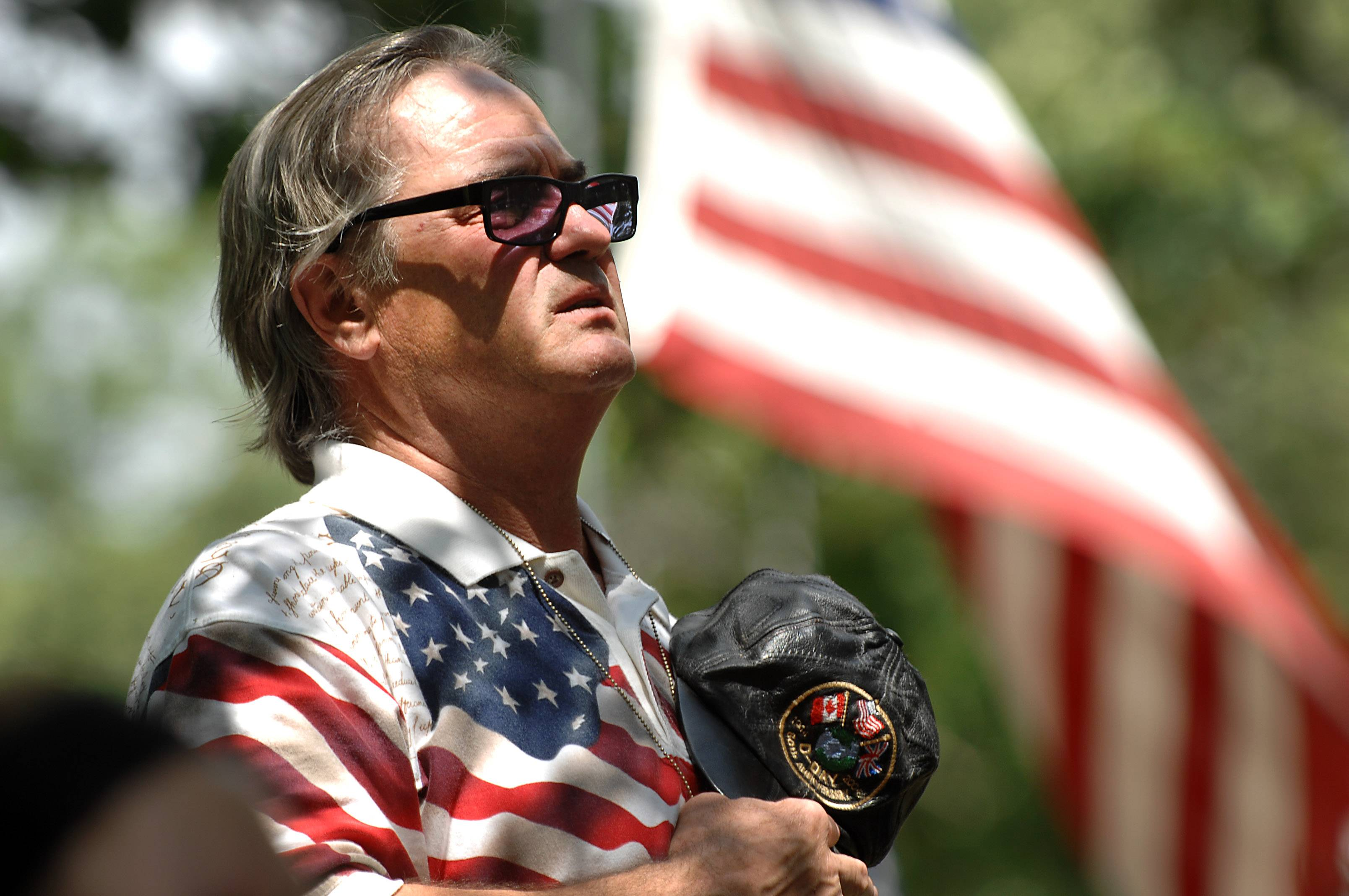 Ralph Johnston Jr. of South Elgin says the Pledge of Allegiance Monday while bearing his father's hat and dog tags at the Memorial Day service at the Bluff City Cemetery in Elgin. His father served in France during World War II.