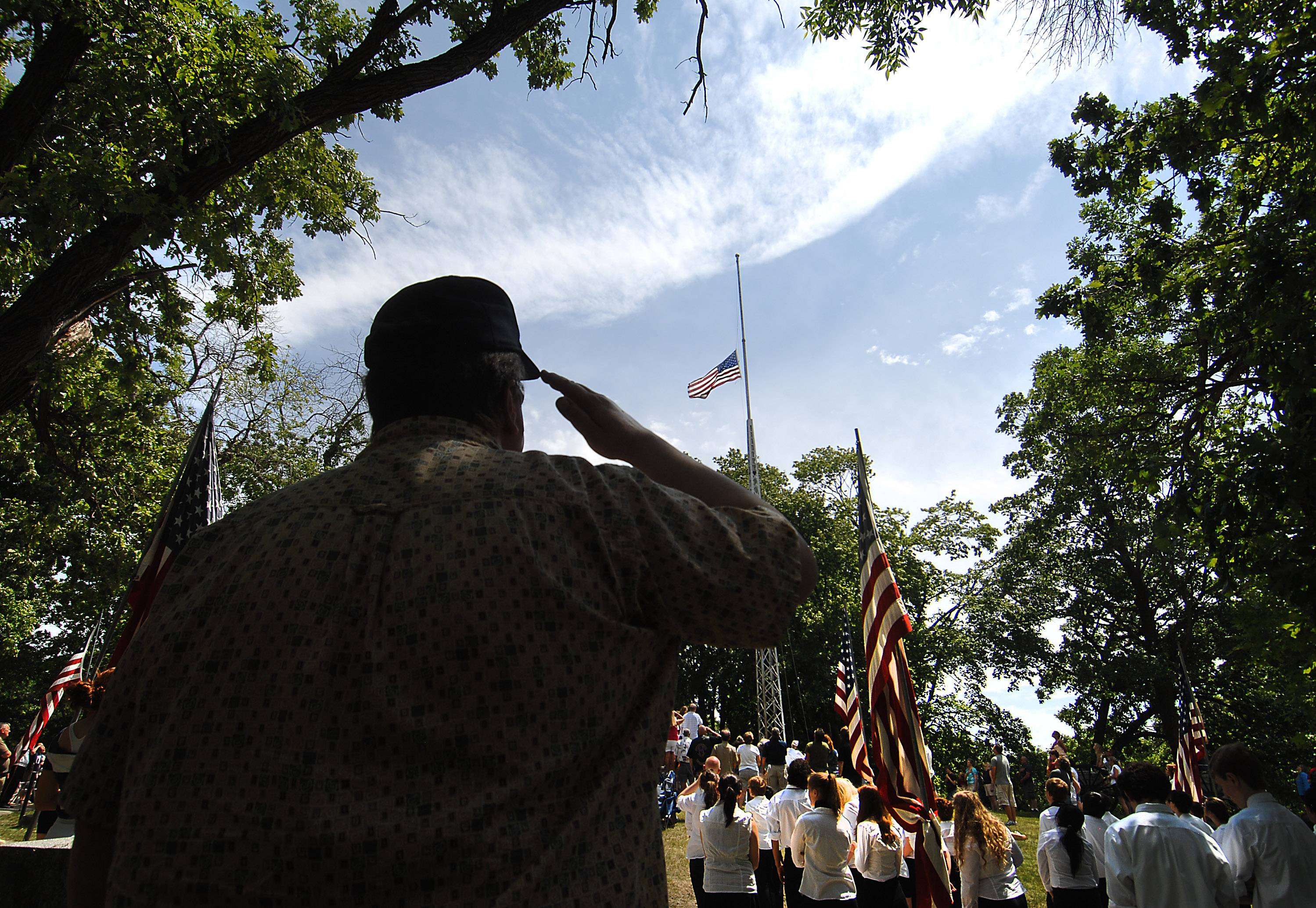 Mark Rodecker of Ship 7 Navy Club of Elgin salutes Monday as the flag is lowered and raised again during the Memorial Day service at the Bluff City Cemetery in Elgin.
