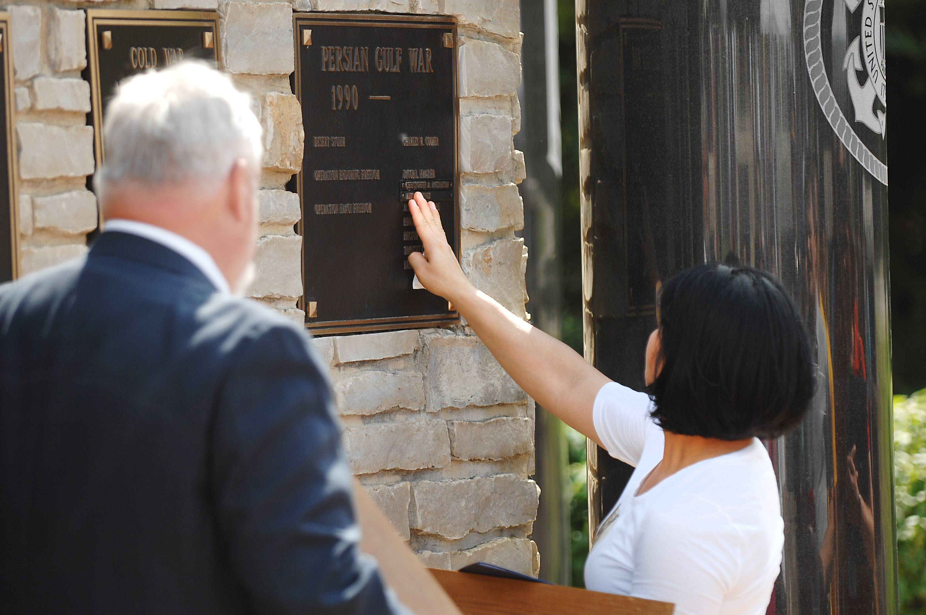 Socorro Martinez, mother of the late Alex Martinez, touches his name, which was added to the Veterans Memorial Monday at the Government Center in Geneva.