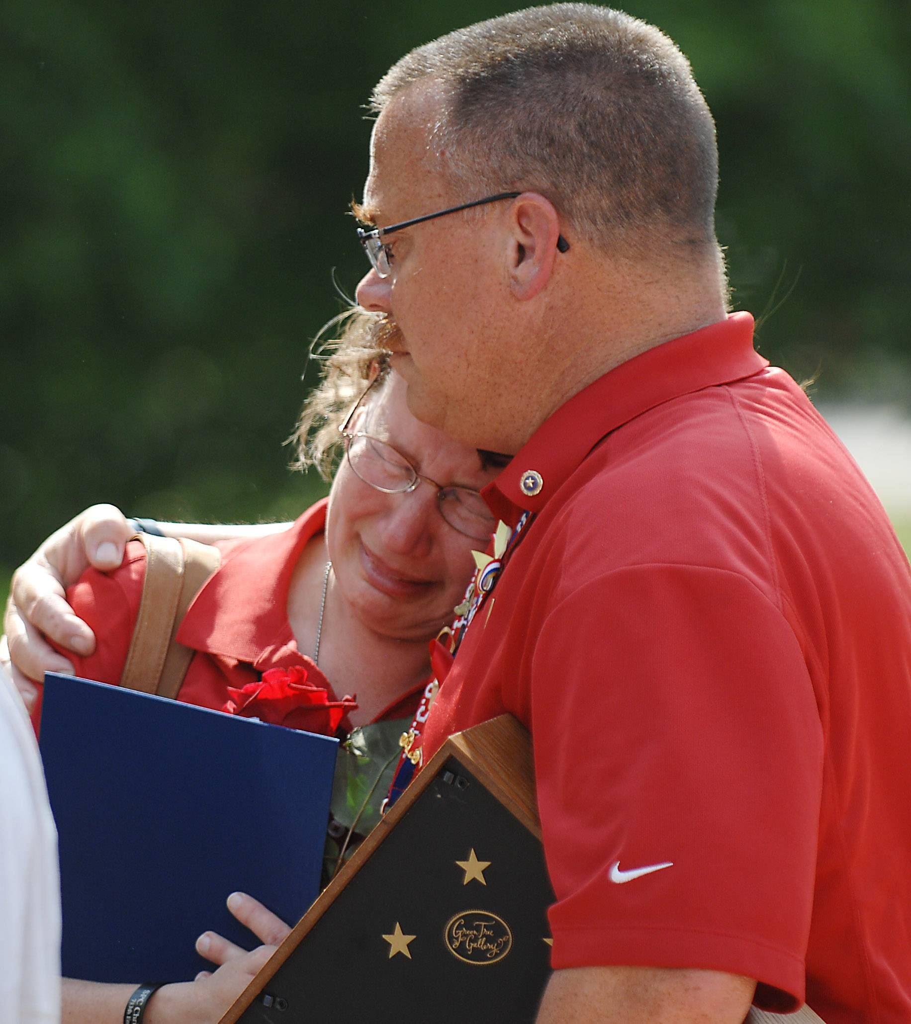 Robert Patterson holds his wife Mary on Monday after their late son, Christopher, was enshrined in the Veterans Memorial at a ceremony sponsored by the Kane County Veterans Assistance Commission at the Government Center in Geneva.
