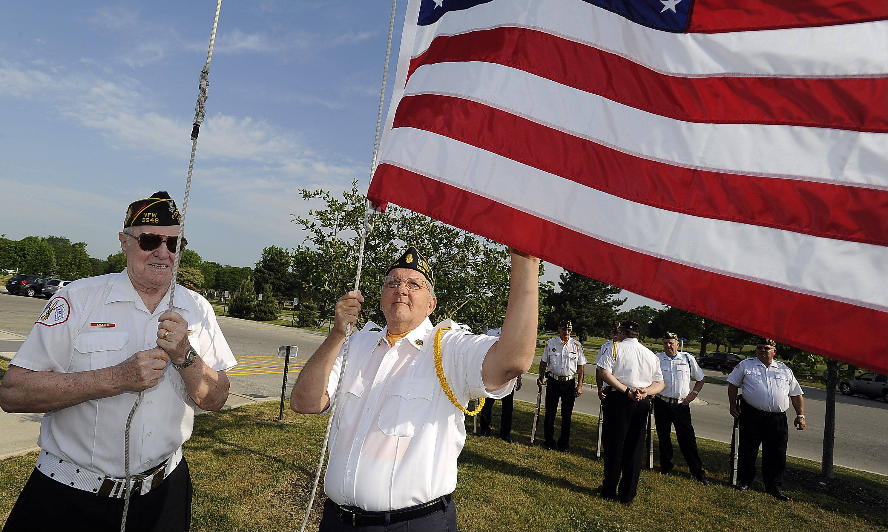 VFW 2992 Officer John Smullen, a veteran of World War II and Korea, along with Officer Ron Simon of American Legion Post 36 raise the flag during the Memorial Day ceremony at All Saints Cemetery in Des Plaines on Monday.