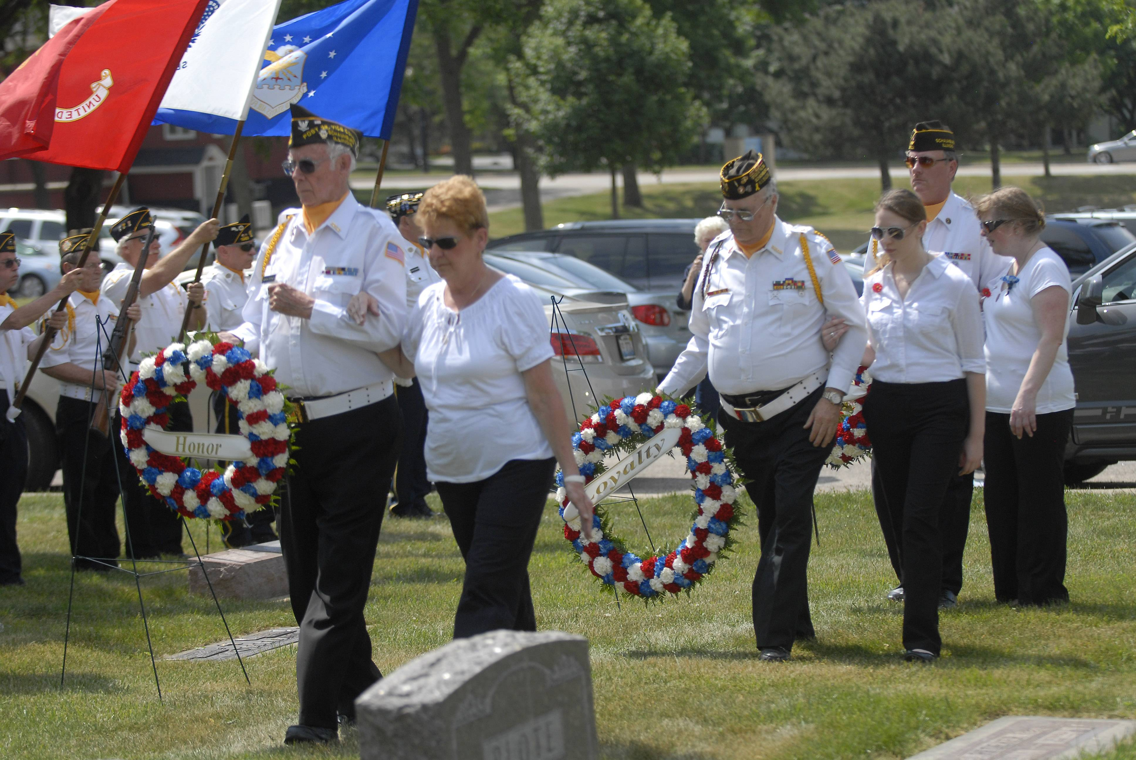 Veterans of Foreign Wars Post 2202 members and ladies auxiliary members -- from left, Gordon Stanley, Georgi Peterson, Marco Dabetic, Samantha Alderson, David Hill and Julie Hill -- place wreathes during the Memorial Day service Monday at the St. Peter's Lutheran Church cemetery in Schaumburg.