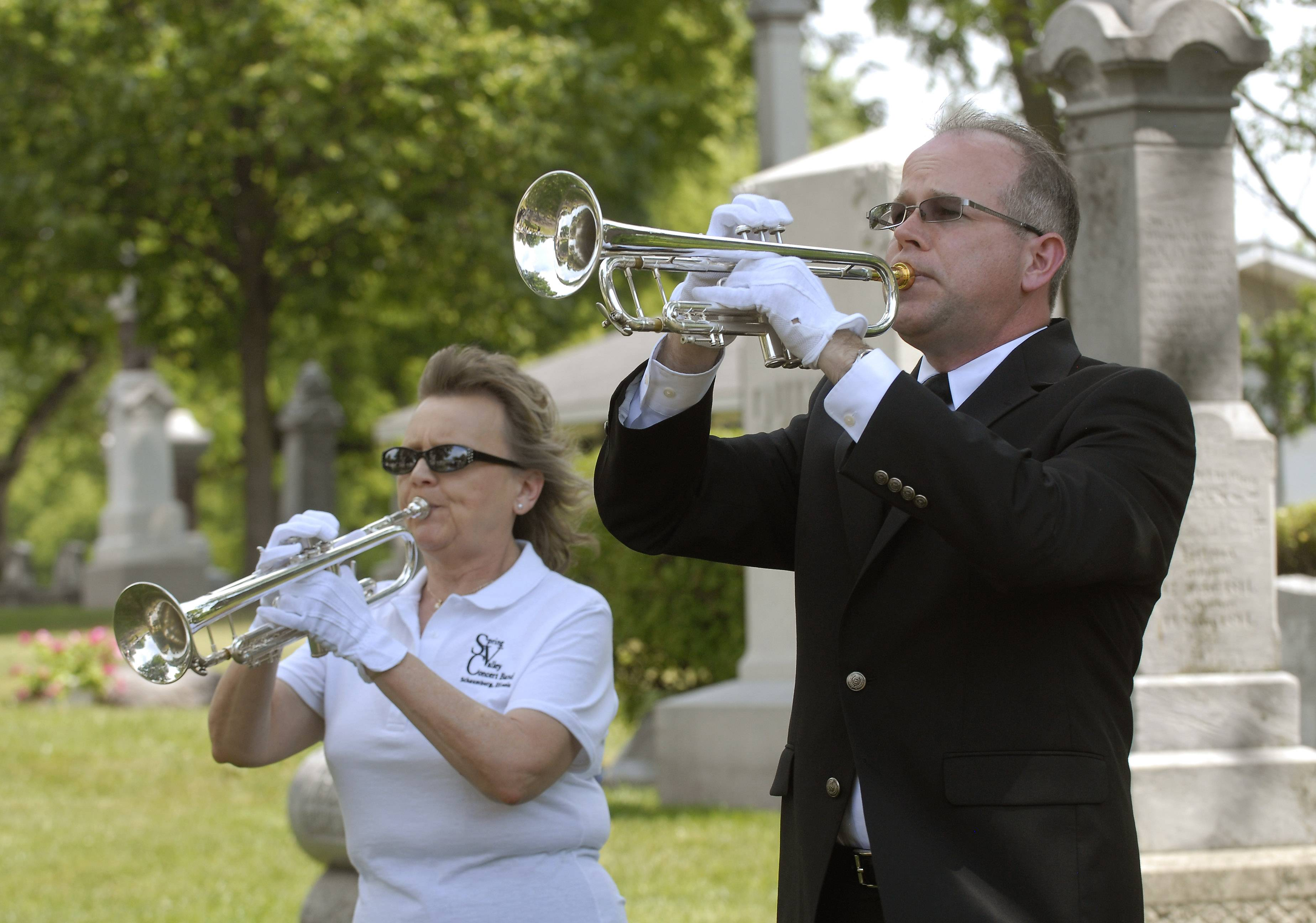 Spring Valley Concert Band members Stephen Foster of Hoffman Estates and Catherine Kapocius of Streamwood play taps during the Memorial Day service Monday at the St. Peter's Lutheran Church cemetery in Schaumburg.