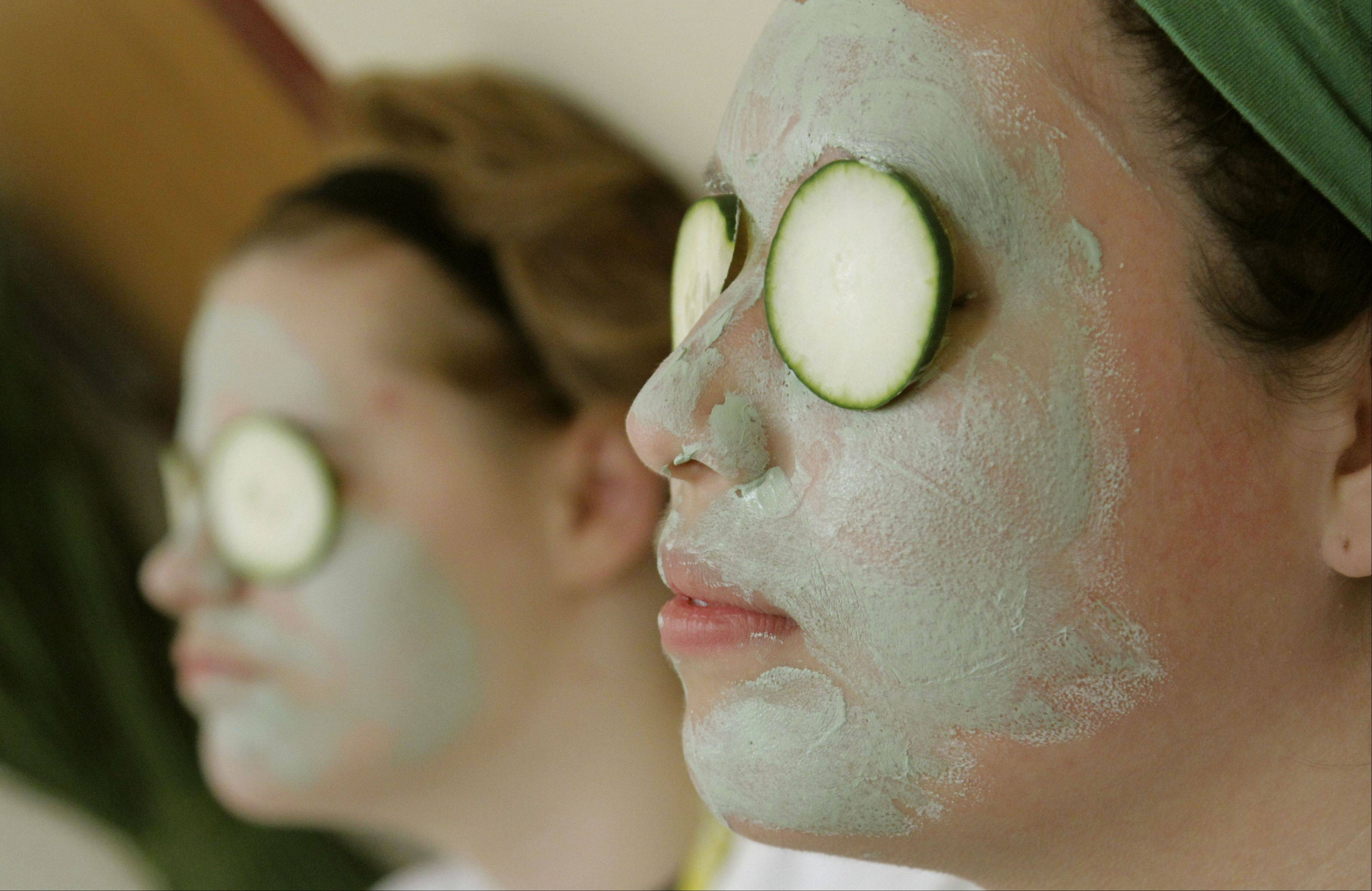 Eighth grade girls Jessica Sweeney, left, and Maria Hernandez get facials as 24 kids were treated to a pampering spa day before attending their annual eighth grade promotion dance Friday at John T. Magee Middle School in Round Lake.