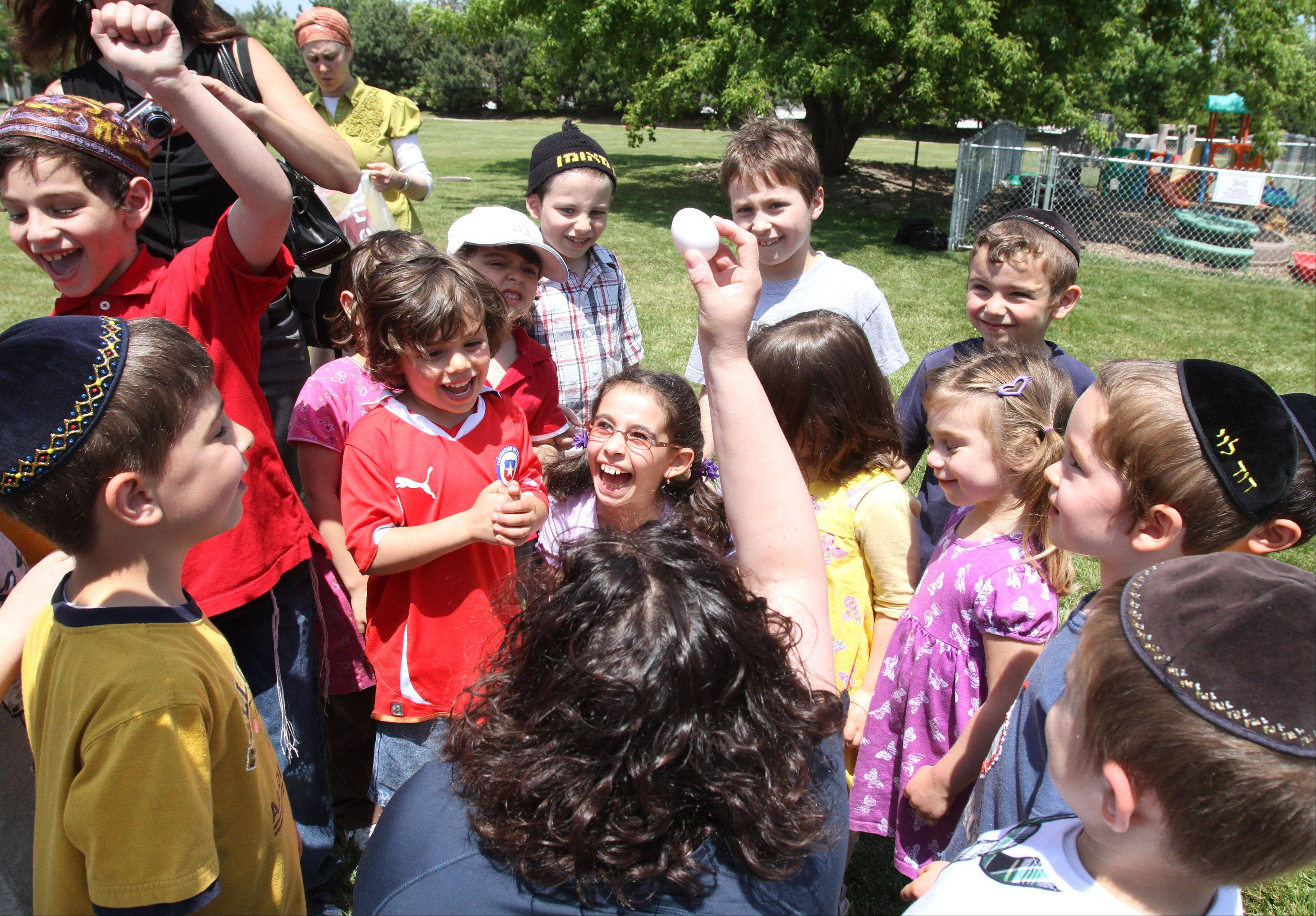 Students at Torah Academy of Buffalo Grove cheer as science coordinator Kimberly Friedman holds up an egg that survived the great egg drop at the school in Buffalo Grove on Thursday, May 24. The students designed and made protective housing for an egg that was then dropped to test if the egg broke.
