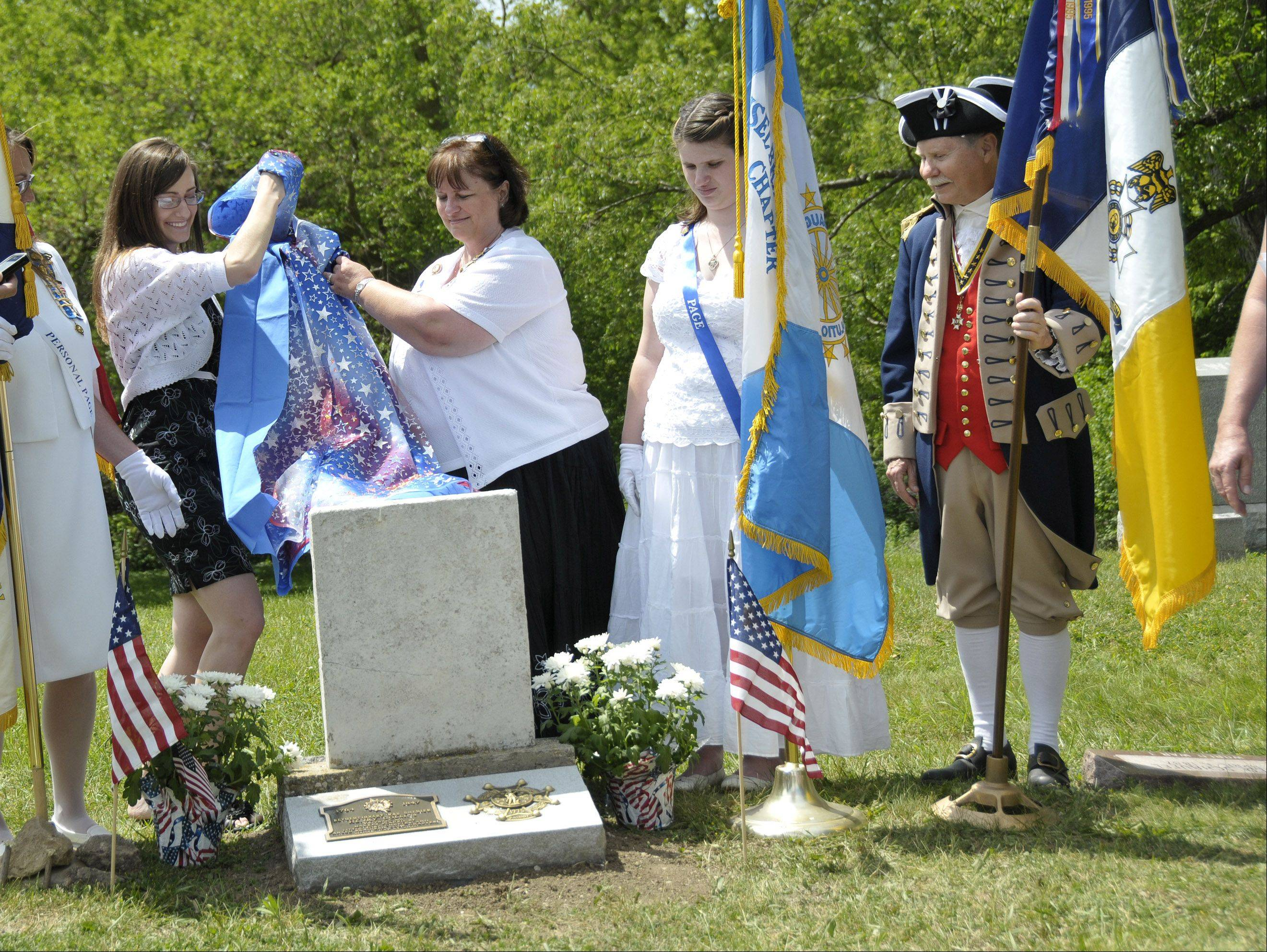 DAR Waukegan Chapter Regent, Hannah Perron, left, and DAR Libertyville Chapter Regent Denise Burja, 2nd left, unveil the new marker on Henry Collins' grave. DAR member Amanda Burja, 2nd right, and SAR member Don Parrish from Naperville, right, look on. Members of the Daughters of the American Revolution from Libertyville and Waukegan, and members of the Sons of the American Revolution from Lisle and Naperville honored Revolutionary War Soldier Henry Collins Friday at his gravesite in Wadsworth. Collins served for two years in the Revolutionary War with a Massachusetts regiment. In 1844, he moved to Lake County with his son Joseph Collins and settled on land in Newport Township. The DAR and SAR have an ongoing project to locate and mark the graves of Revolutionary War Soldiers in Illinois.
