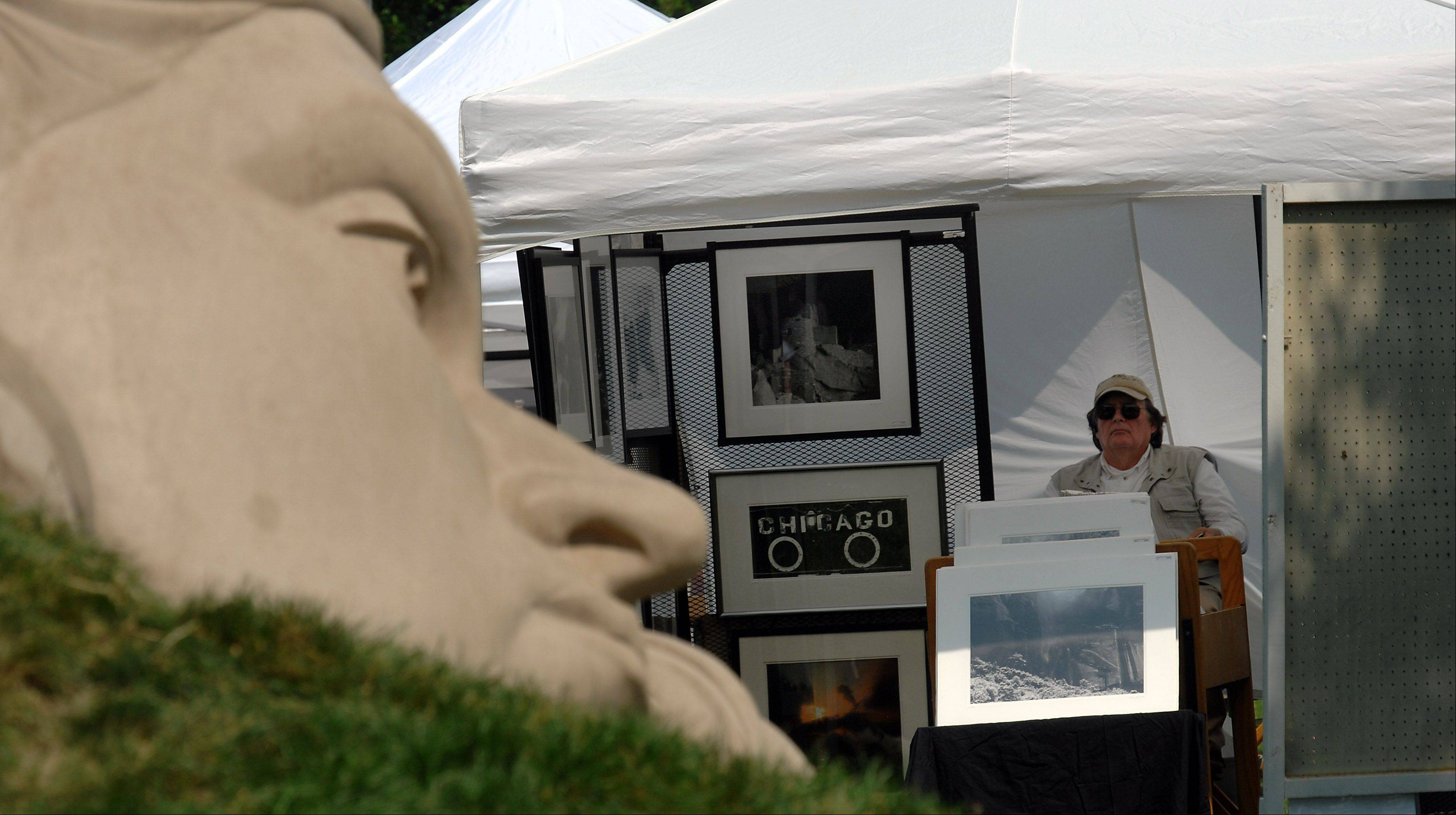James Hojnacki of Hoffman Estates waits for patrons to view his photography work at the Schaumburg Prairie Arts Festival on Saturday.