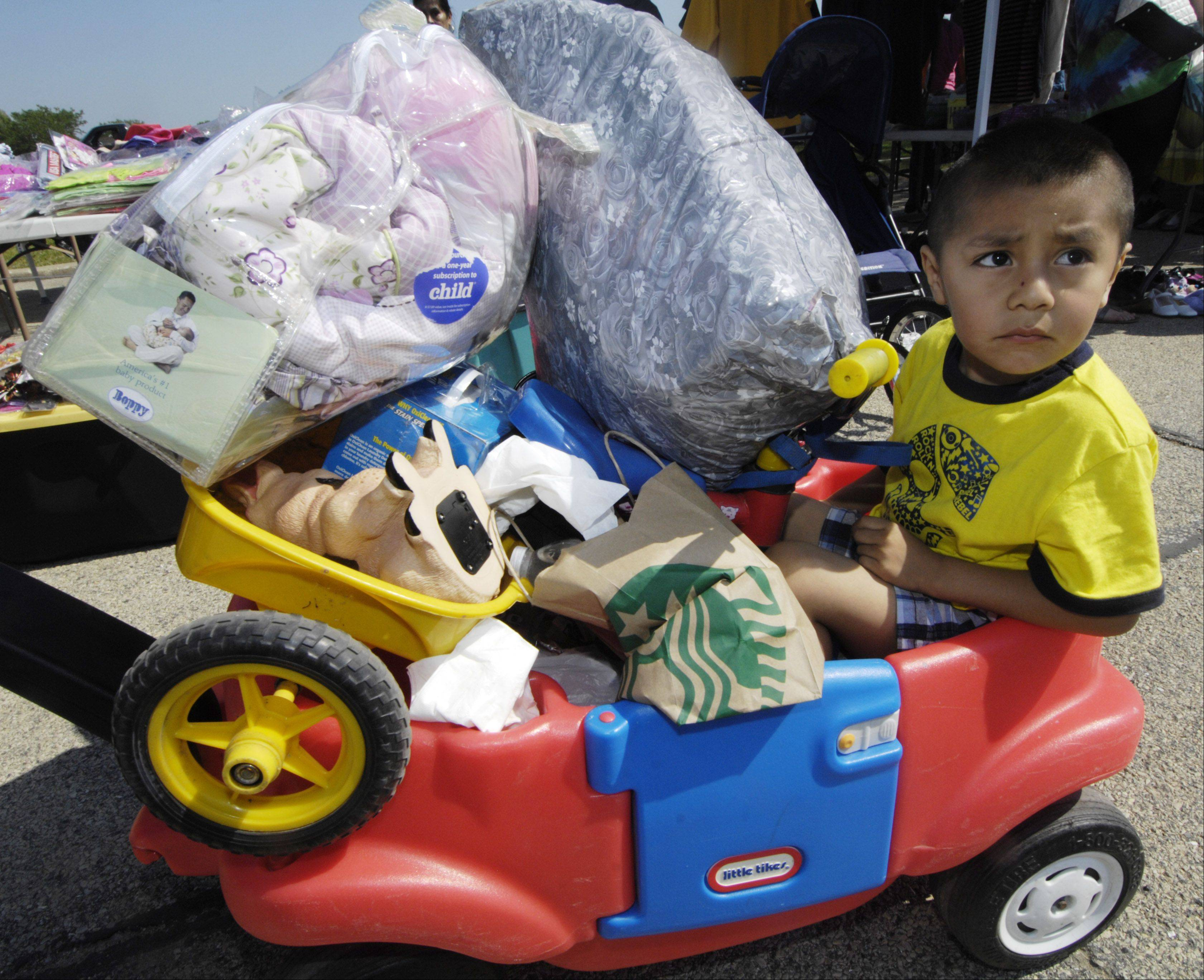 Joshua Tolentino, 4, rides along with his mother's purchases during Hanover Park's Maxwell Street garage sale held at the commuter parking lot Saturday.