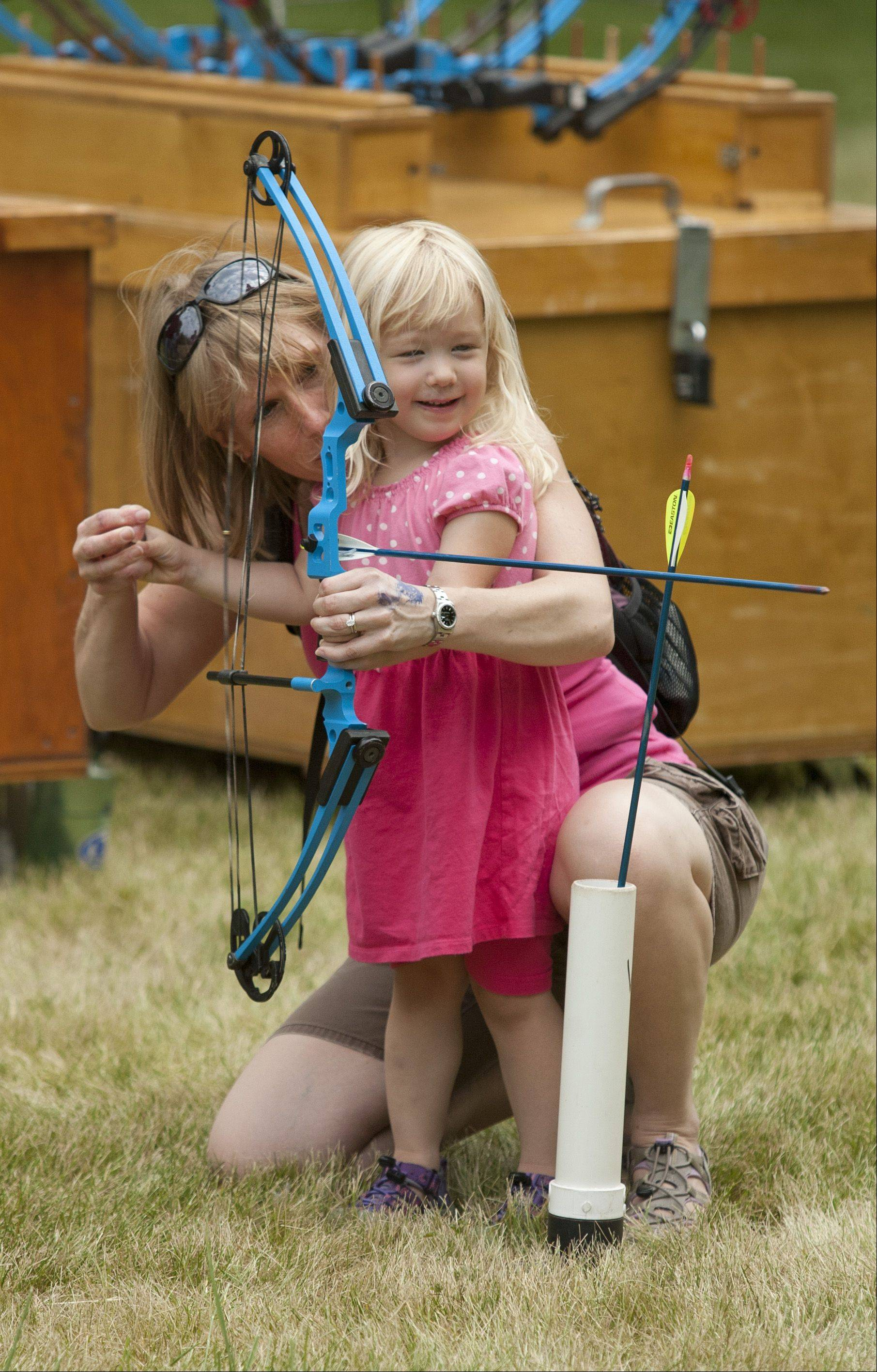 "Piper Patchik, 3, and her mother Jessica Patchik, of Aurora, perfect their archery techniques during the DuPage Forest Preserve District's ""Family Field Day"", held at St. James Farm in Warrenville."