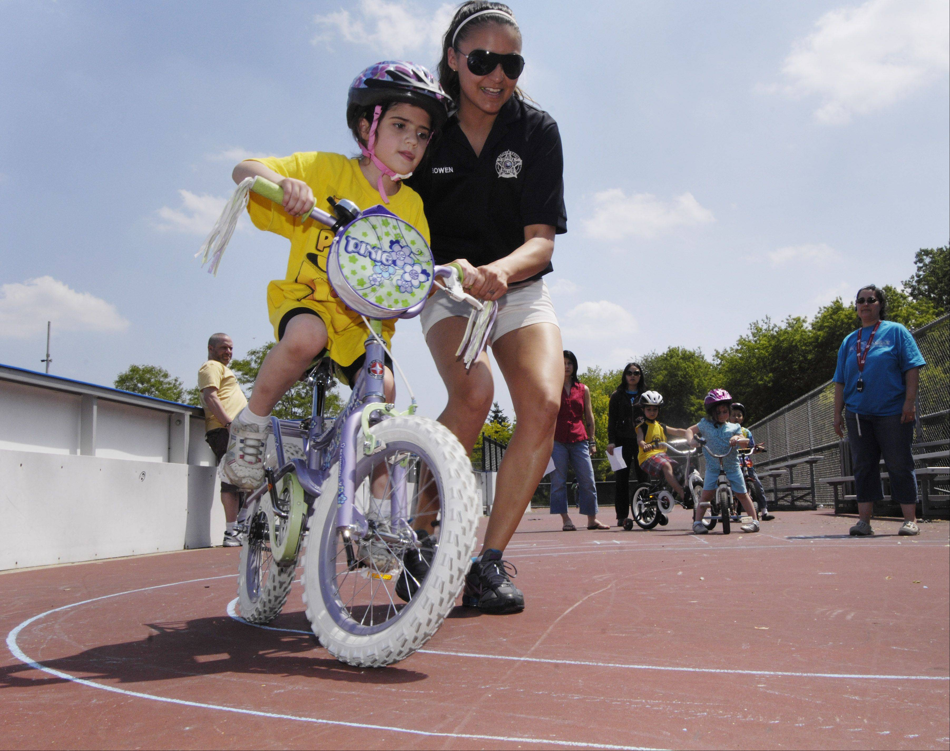 Miranda Logan, 6, of Buffalo Grove gets a little help from police officer Crystal Bowen as she completes a figure eight during Saturday's Buffalo Grove bicycle rodeo at Mike Rylko Park.