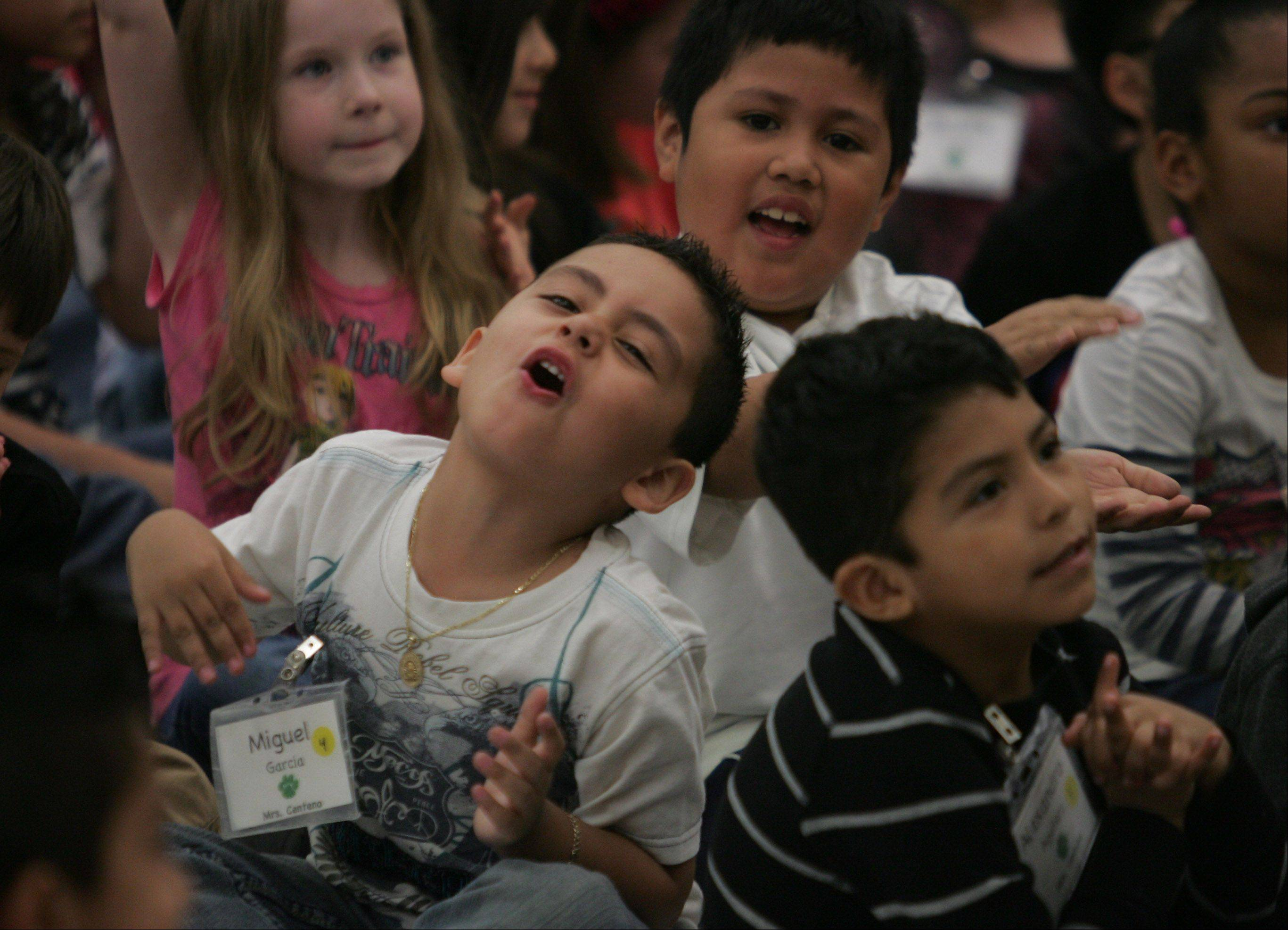 Kindergartners Miguel Garcia, left, Isaac Morales and Alexandro Aguilera dance to the music as ScribbleMonsters perform for students at Woodland Primary School Monday in Gages Lake. ScribbleJim and ScribbleJayne used songs and music to bring out the imagination in the kids.