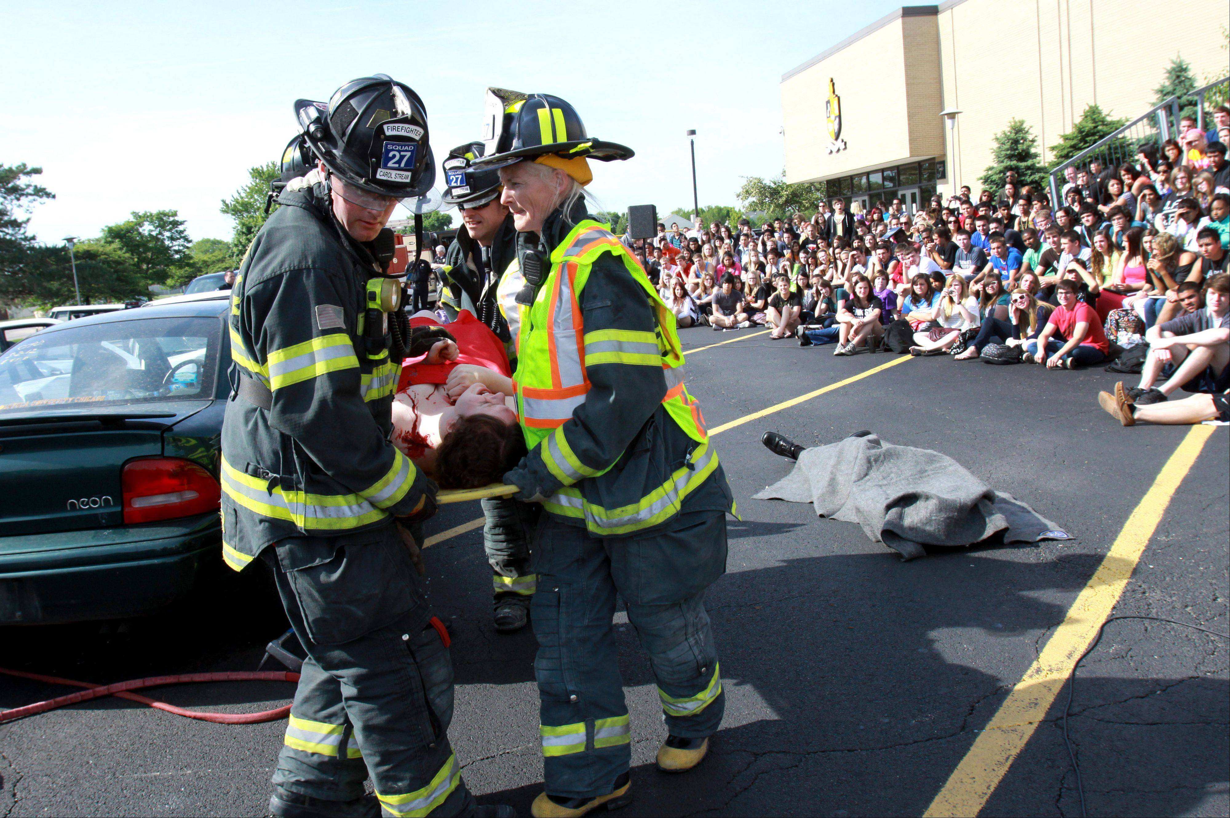 "Seniors look on as firefighters take ""victim"" Beth Cerabona out of a car during a fatal DUI crash scene at Glenbard North High School in Carol Stream on Wednesday. The annual event was put on by the Carol Stream Police Department and the Carol Stream Fire Protection District ahead of the school's prom this Saturday. Eight students, all good friends, played roles in the crash with two students DOA. ""It was scary and really terrifying"", said Cerabona of playing the victim and seeing her friends in the crash scenario."