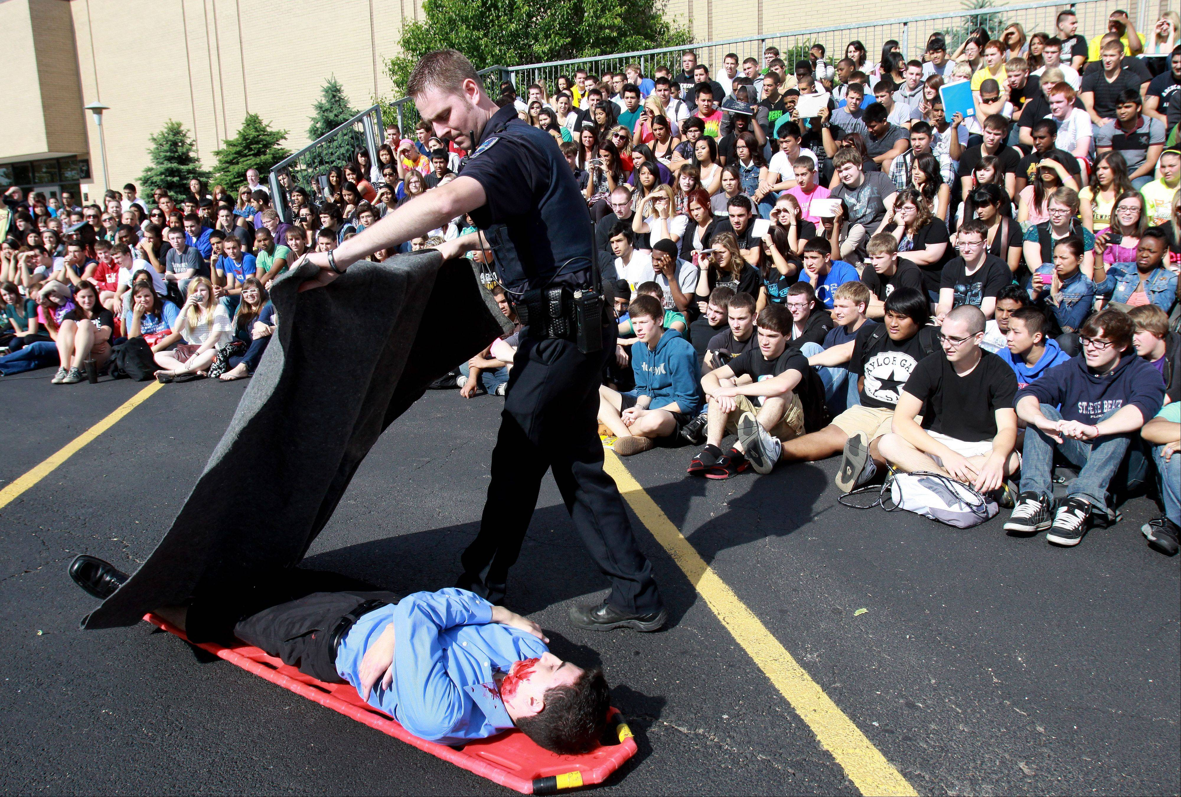 Senior Michael Fagen plays a DOA victim during a fatal DUI crash scene at Glenbard North High School in Carol Stream on Wednesday. The annual event was put on by the Carol Stream Police Department and the Carol Stream Fire Protection District ahead of the school's prom this Saturday.