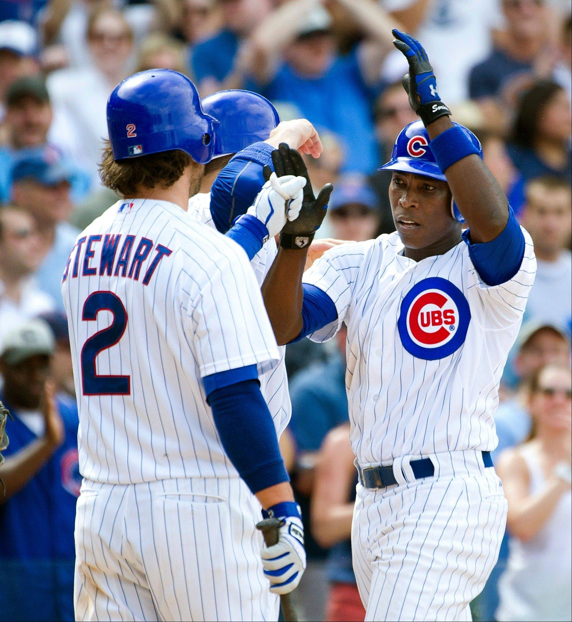 From left, Cubs players Ian Stewart and Bryan LaHair congratulate Alfonso Soriano after Soriano hit a two-run home run to score LaHair during Monday's sixth inning at Wrigley Field.