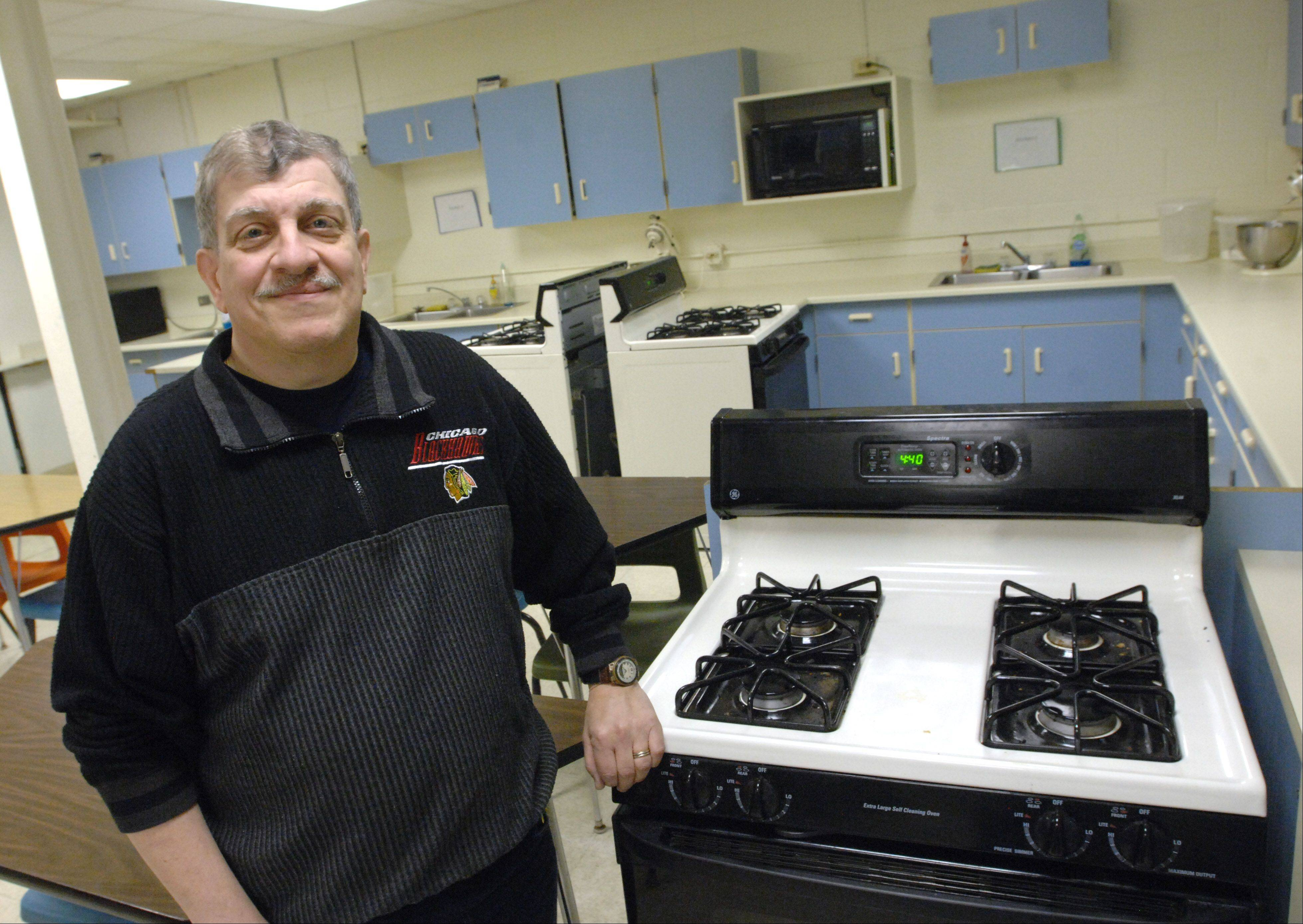 Chuck Federici takes a break from maintenance duties at Fenton High School to whip up lasanga in the home economics classroom.